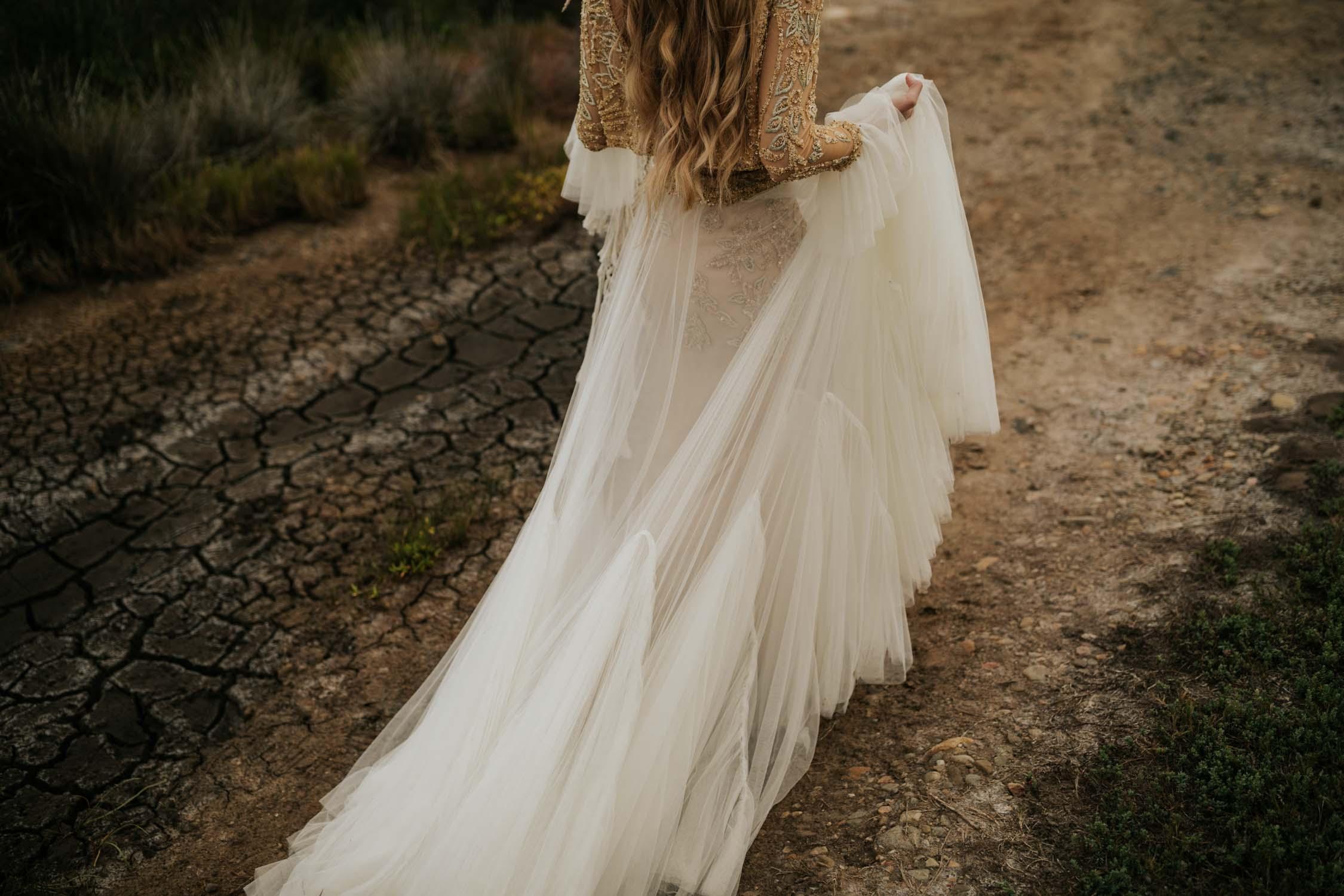 Beautiful boho gypsy bride walks on dried river bed