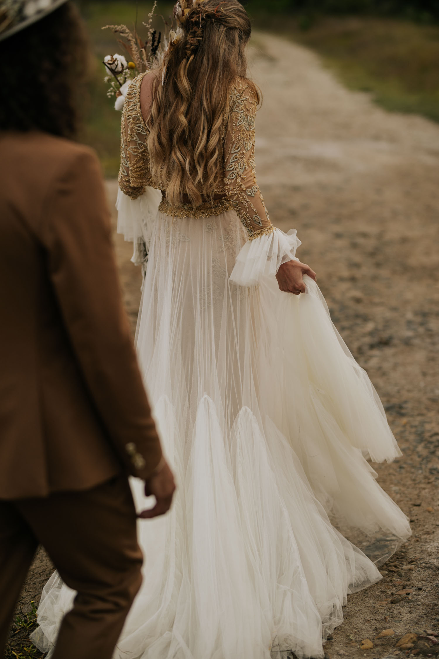 Boho bride wears feather ear cuff and hair piece and a wedding dress with flared long sleeves, sheer skirt and gold detailed top with plait in hair and cotton plant in bouquet