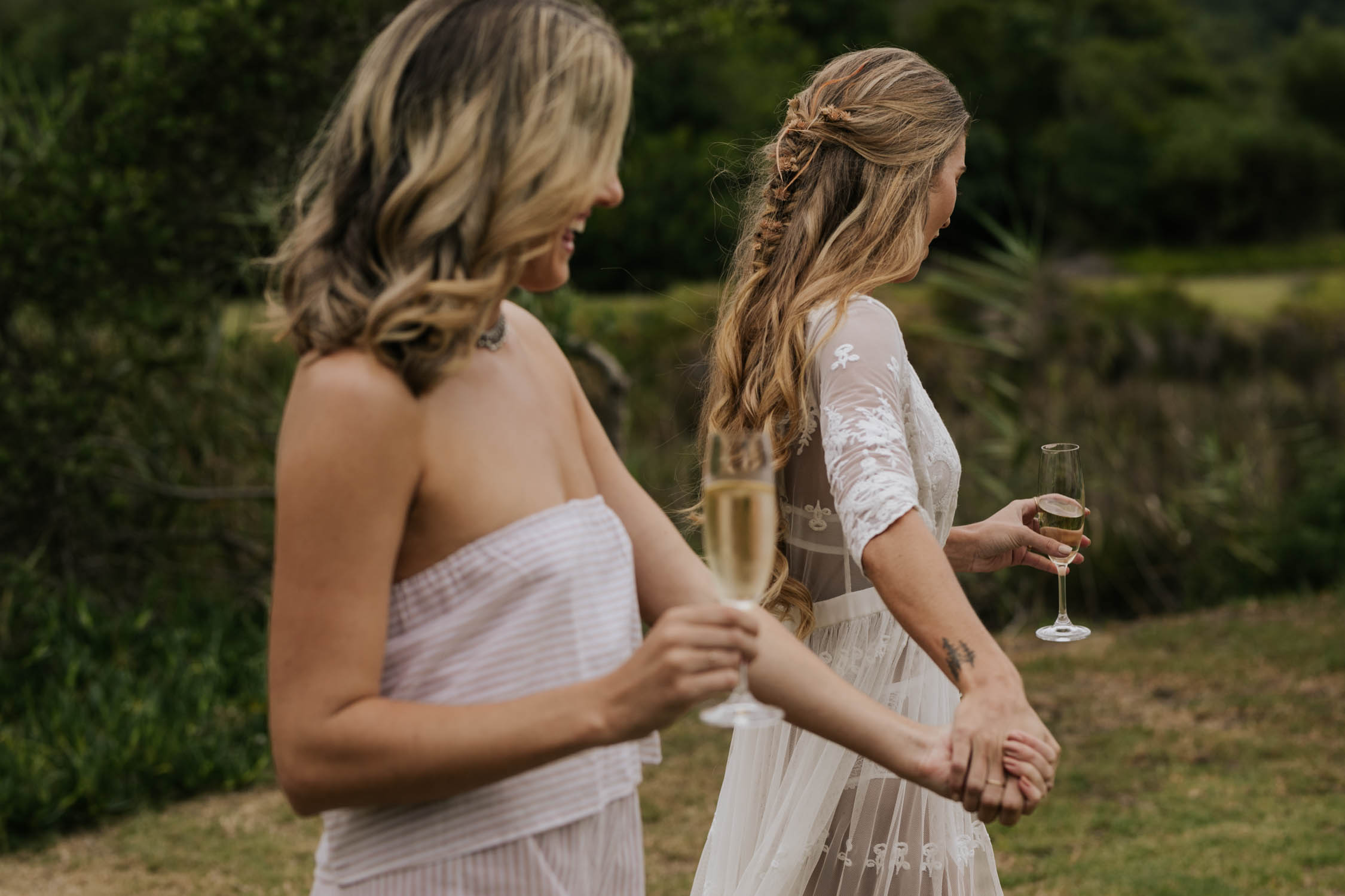 Beautiful Boho bride with long curly hair and gypsy plait dressed in white lace PJs and gown dances and drinks champagne with her bridesmaid