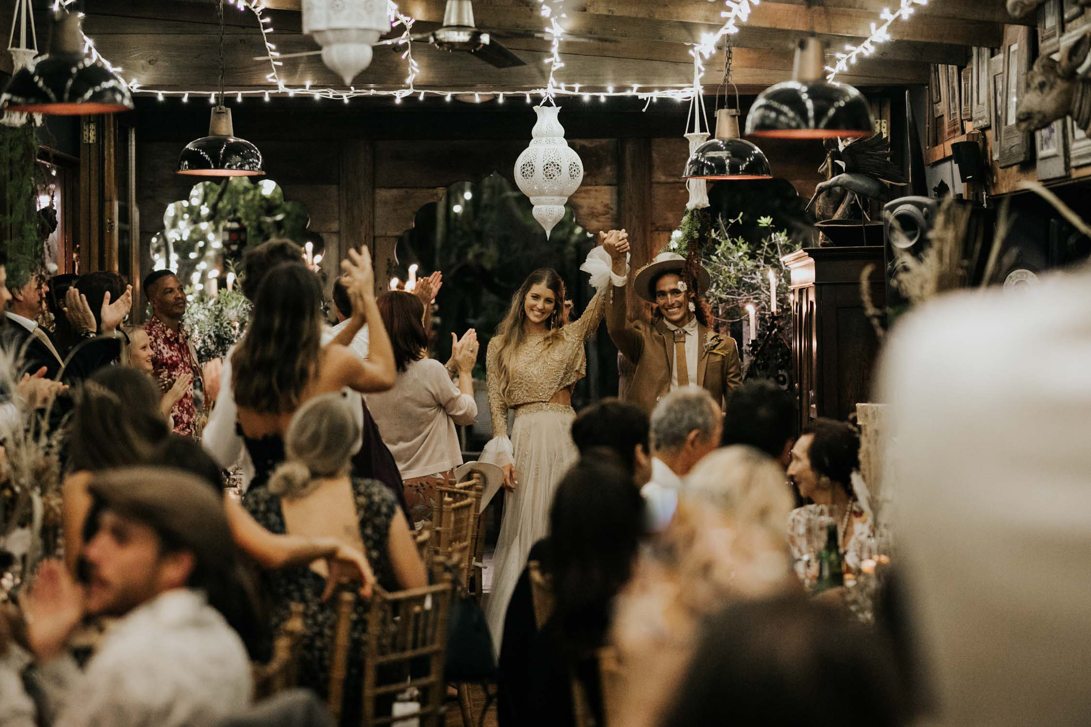 Guest cheer and clap as boho bride and groom enter their wedding reception