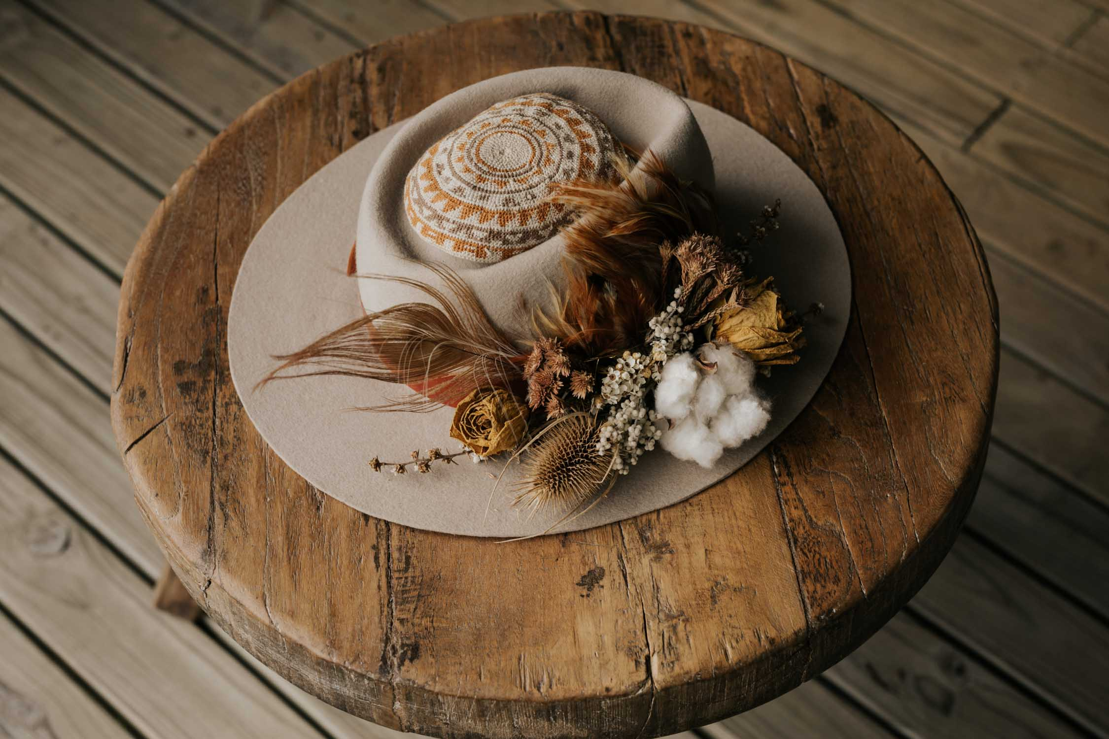 Boho groom's brown felt hat decorated with natural feathers, foraged dried flowers and cotton