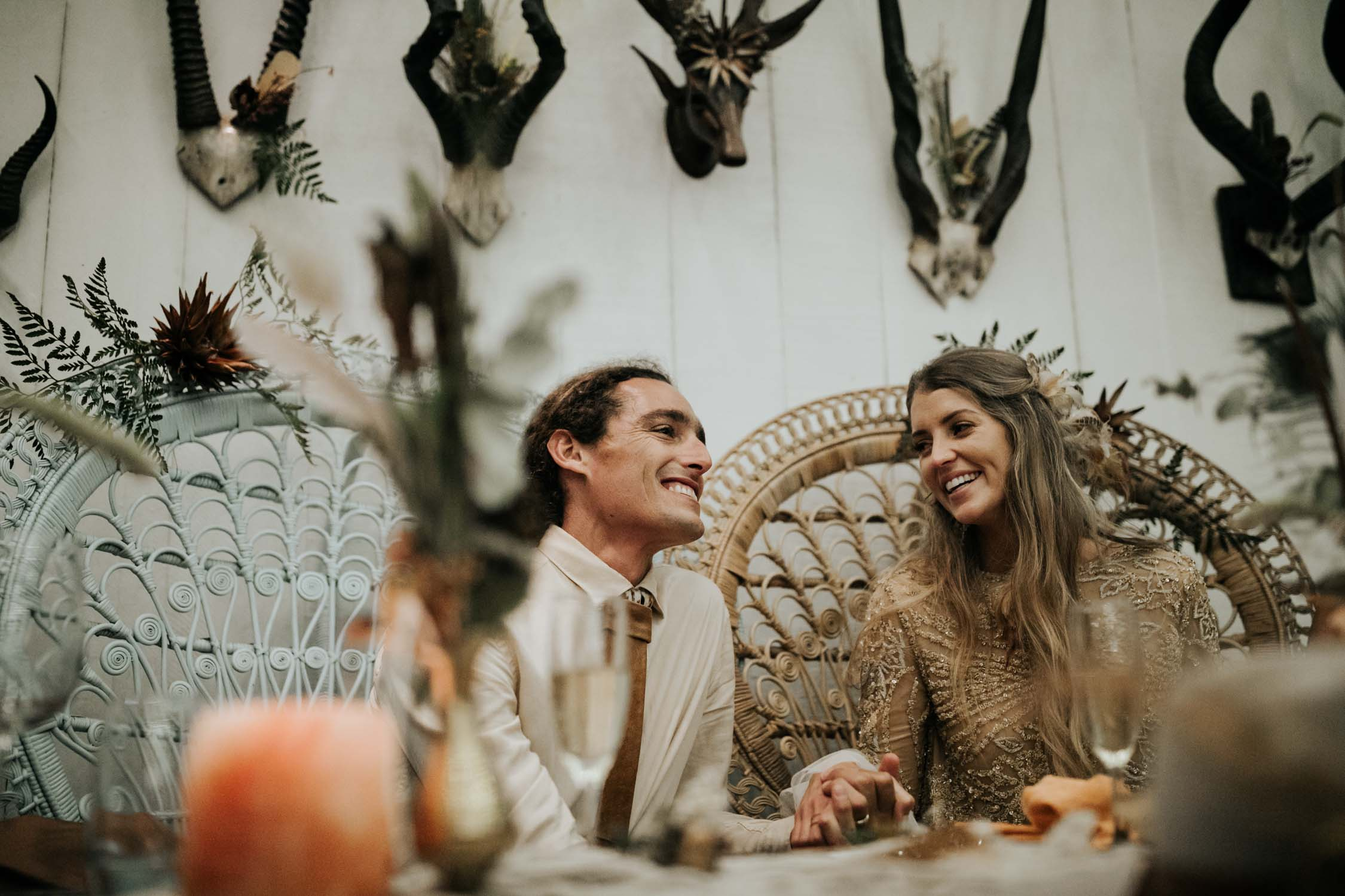 Bride and groom laugh sitting in Bali Boho Wicker Peacock Chairs during wedding speech