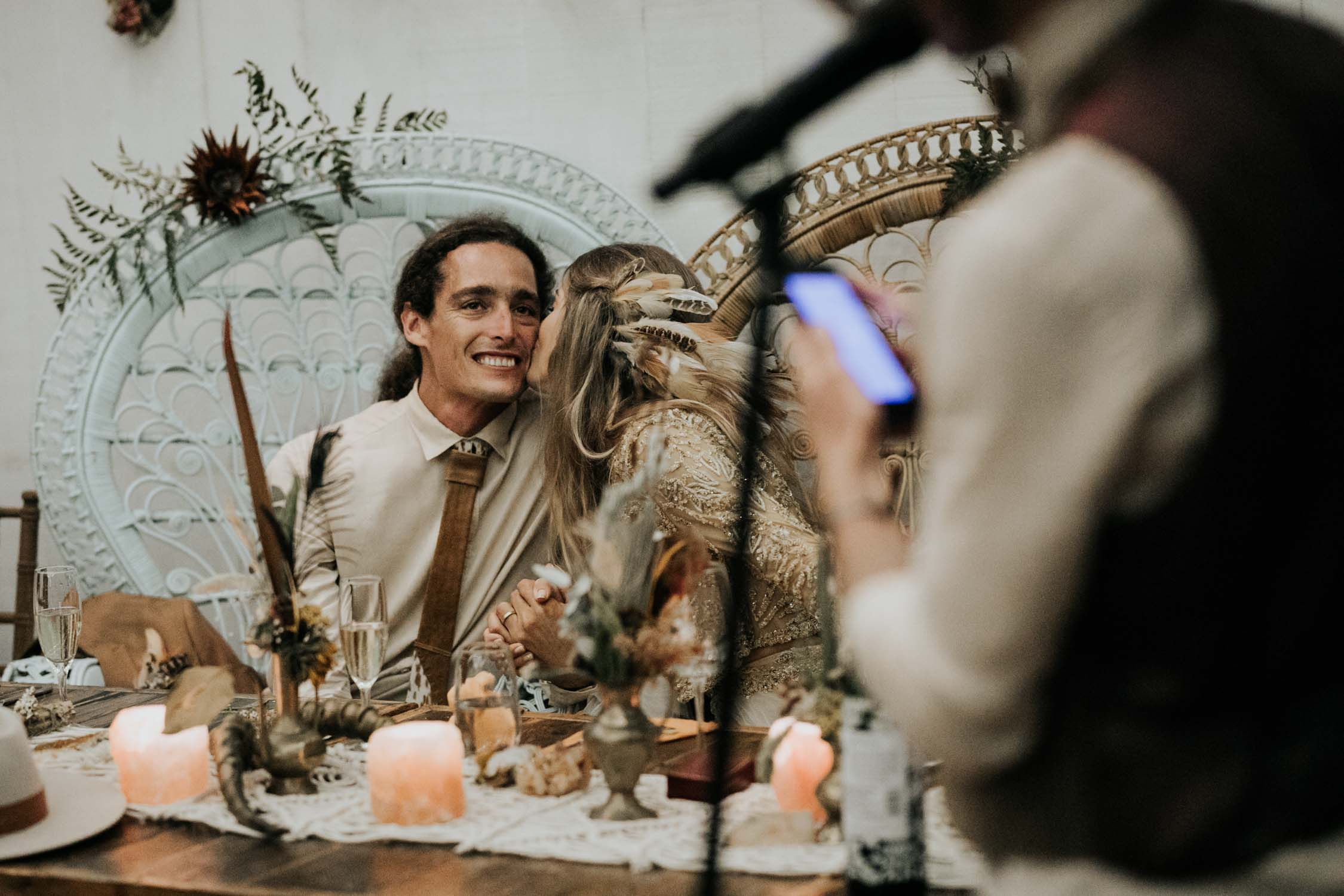 Bride kisses groom on cheek sitting in Bali Boho Wicker Peacock Chairs during wedding speech