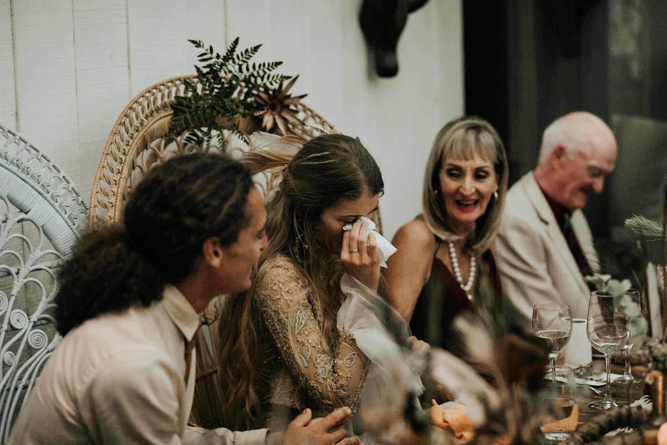 Bride cries sitting in Bali Boho Wicker Peacock Chairs during wedding speech