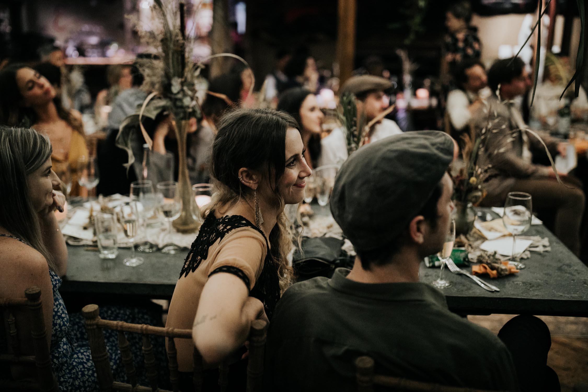 Natural light photo of guests in wedding reception at night by Vancouver Wedding Photographer