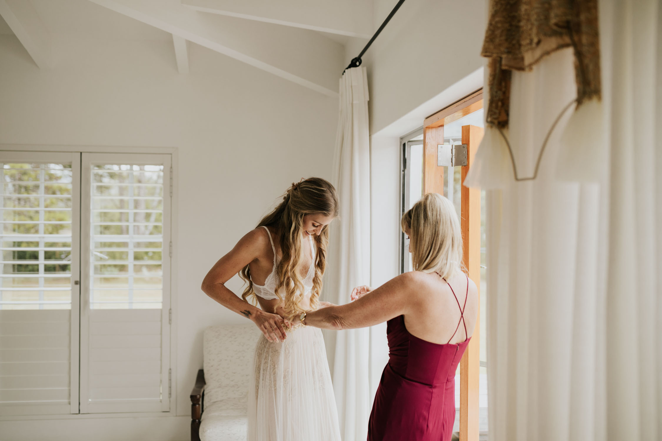 Mother helps bride get into her boho flared sleeved gold and cream wedding dress