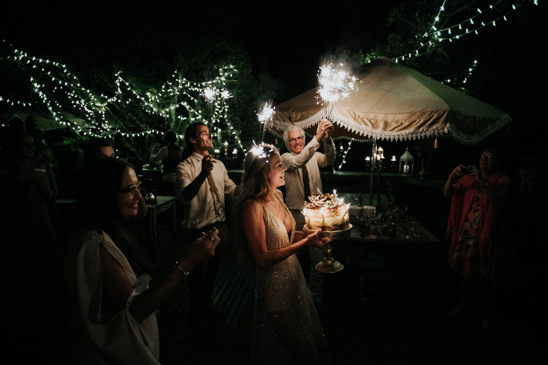 Bride with surprise birthday cake from bridesmaid