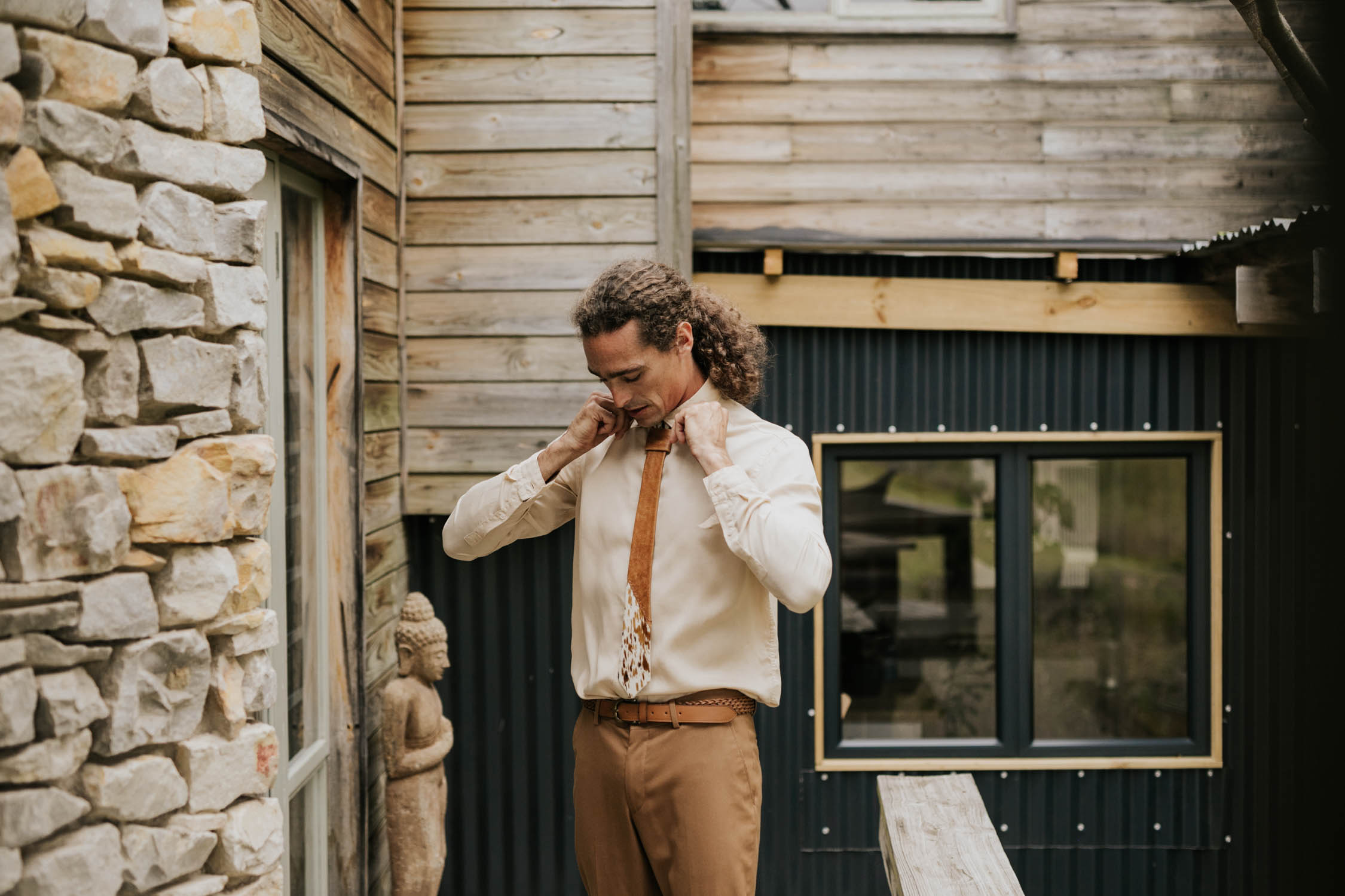 Boho groom with long dark curly hair puts on Nguni cowhide leather tie, brown pants and a beige shirt