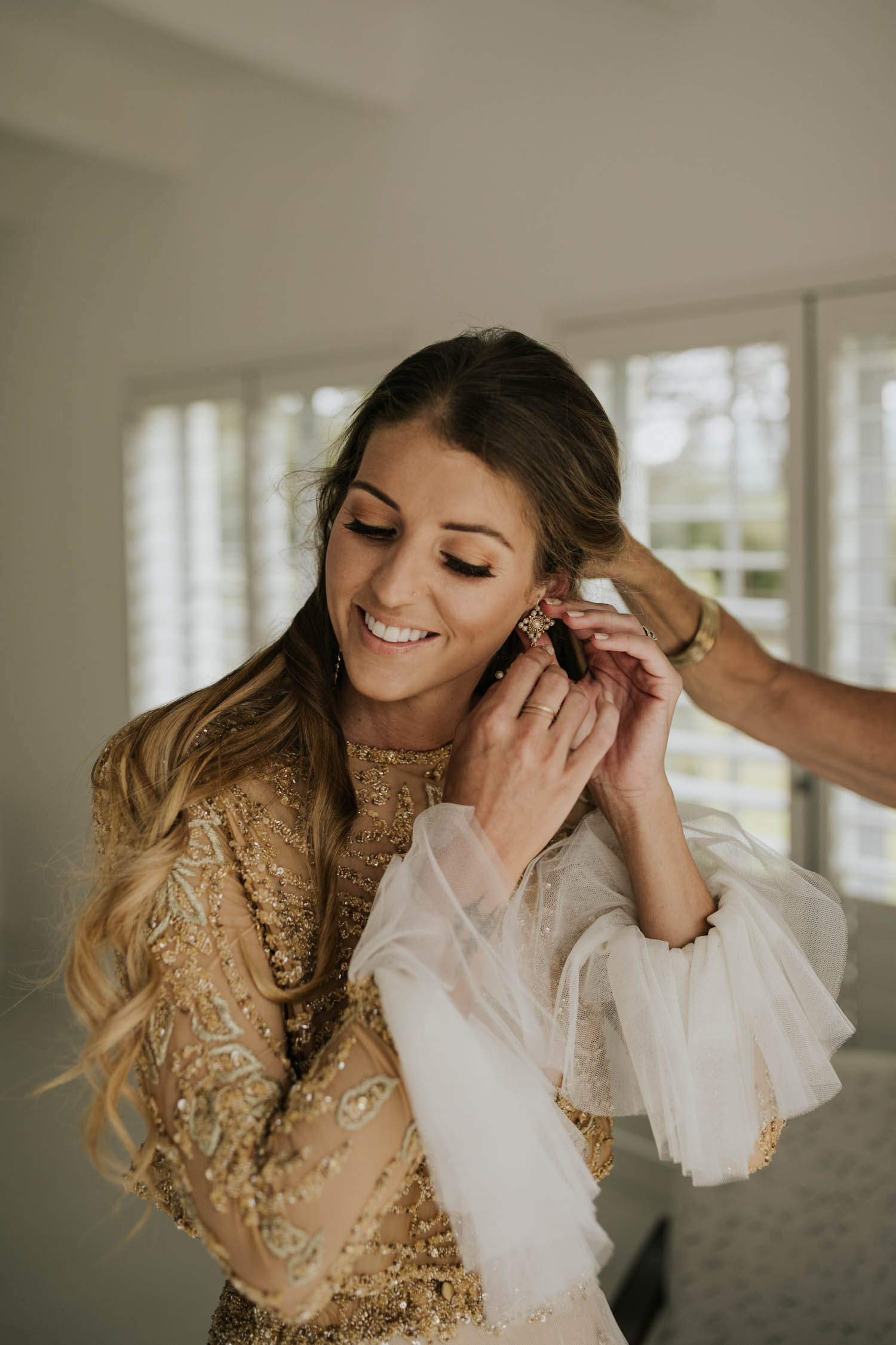 Bohemian bride with long curly blonde hair wearing gold detail long sleeve wedding dress puts on Bo and Luca earrings