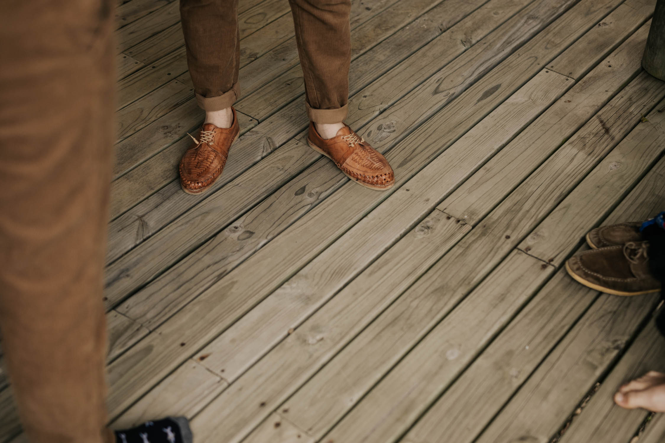 Boho groom puts on woven brown leather wedding shoes