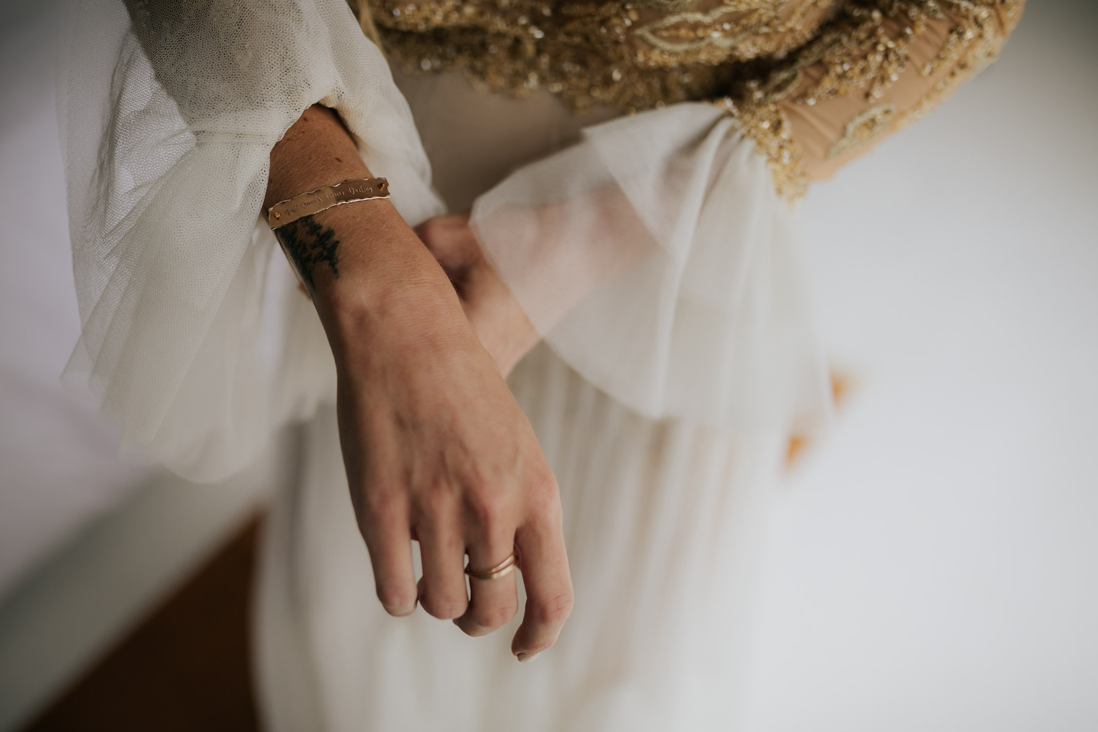 Bohemian bride with long curly blonde hair wearing gold detail long sleeve wedding dress puts on handmade bracelet - a present from the groom