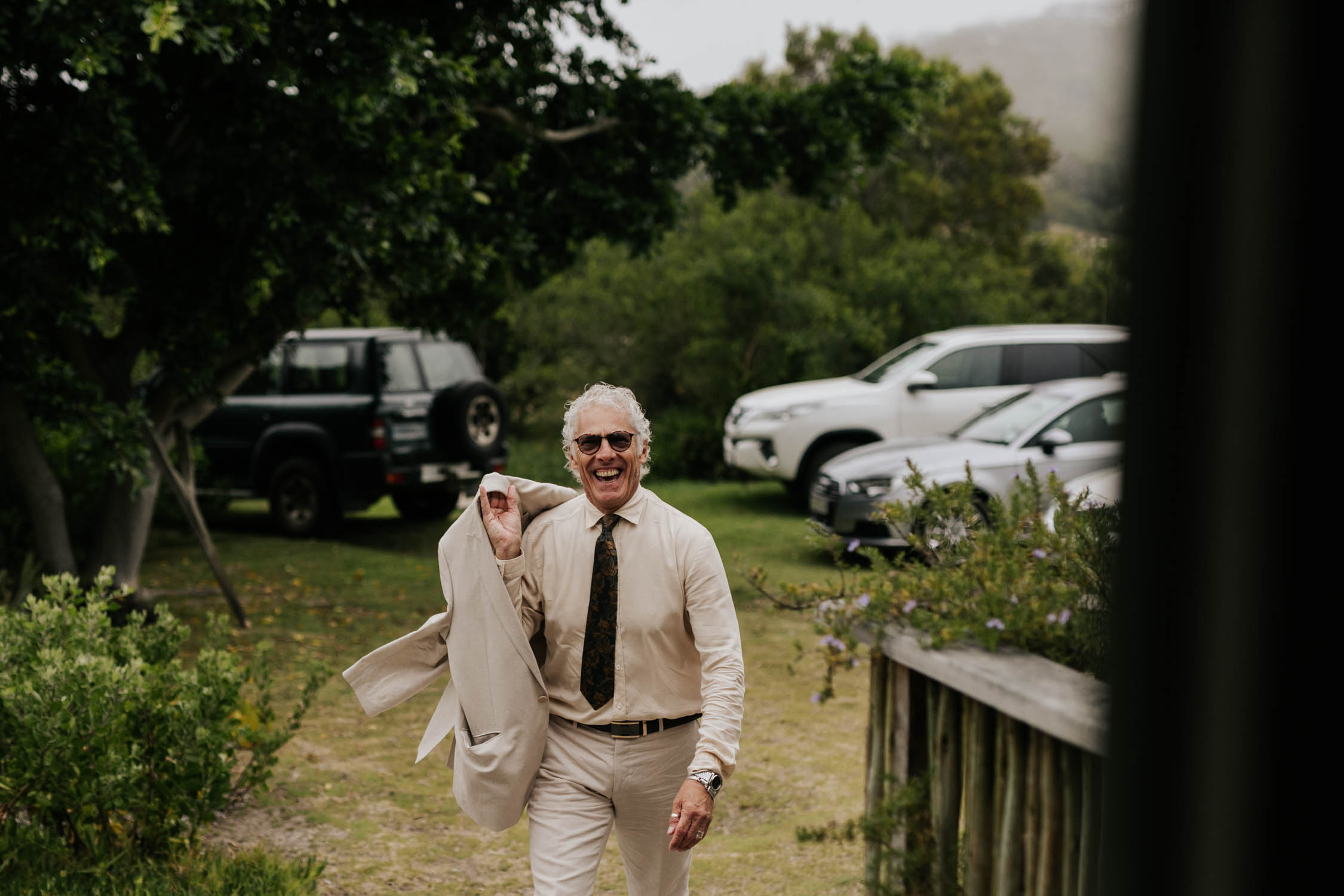 Father of the groom wearing trendy beige suite arrives at The River House at Emily Moon River Lodge