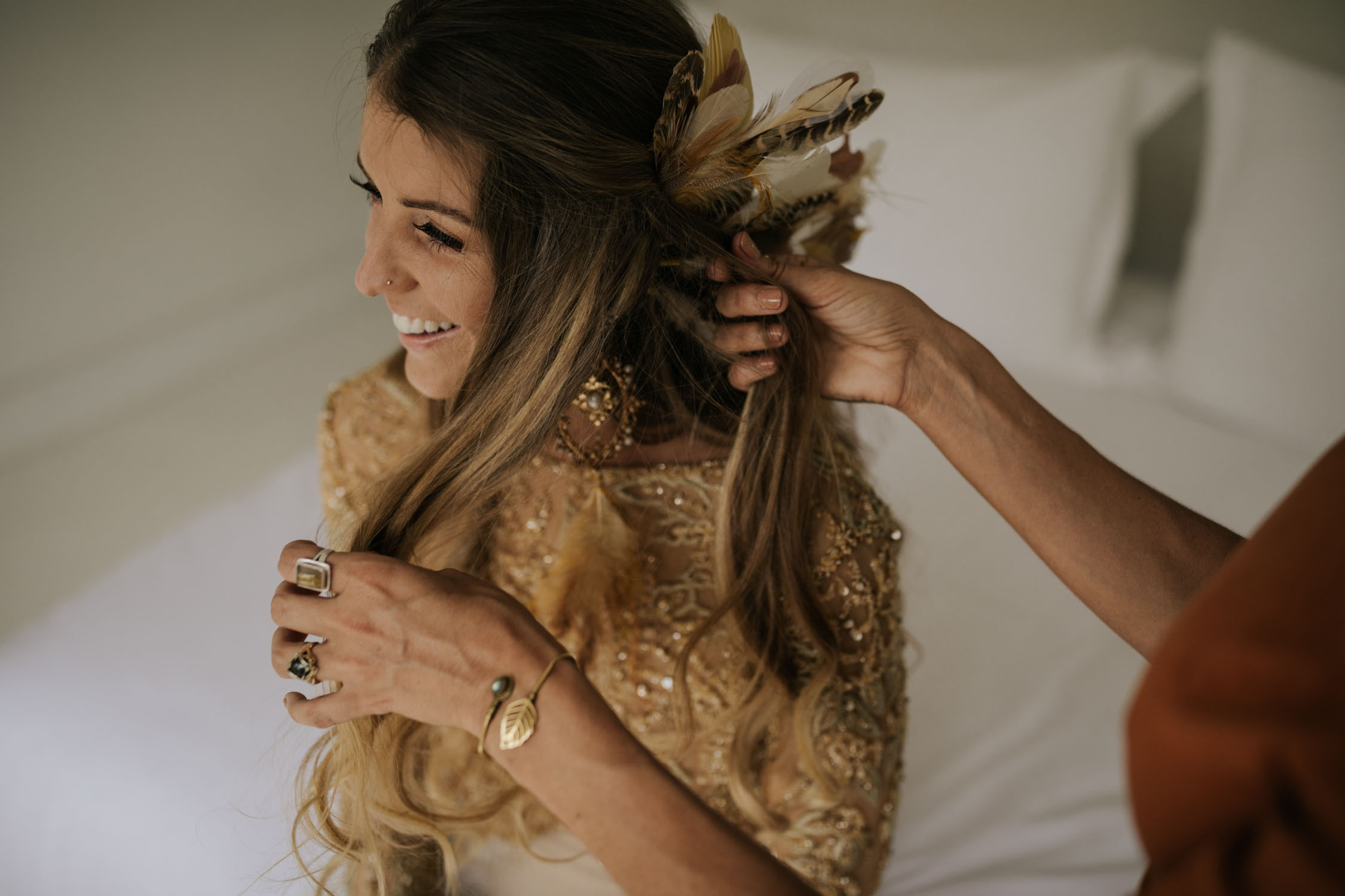 Bohemian bride with long curly blonde hair wearing gold detail long sleeve wedding dress puts on feather ear cuff