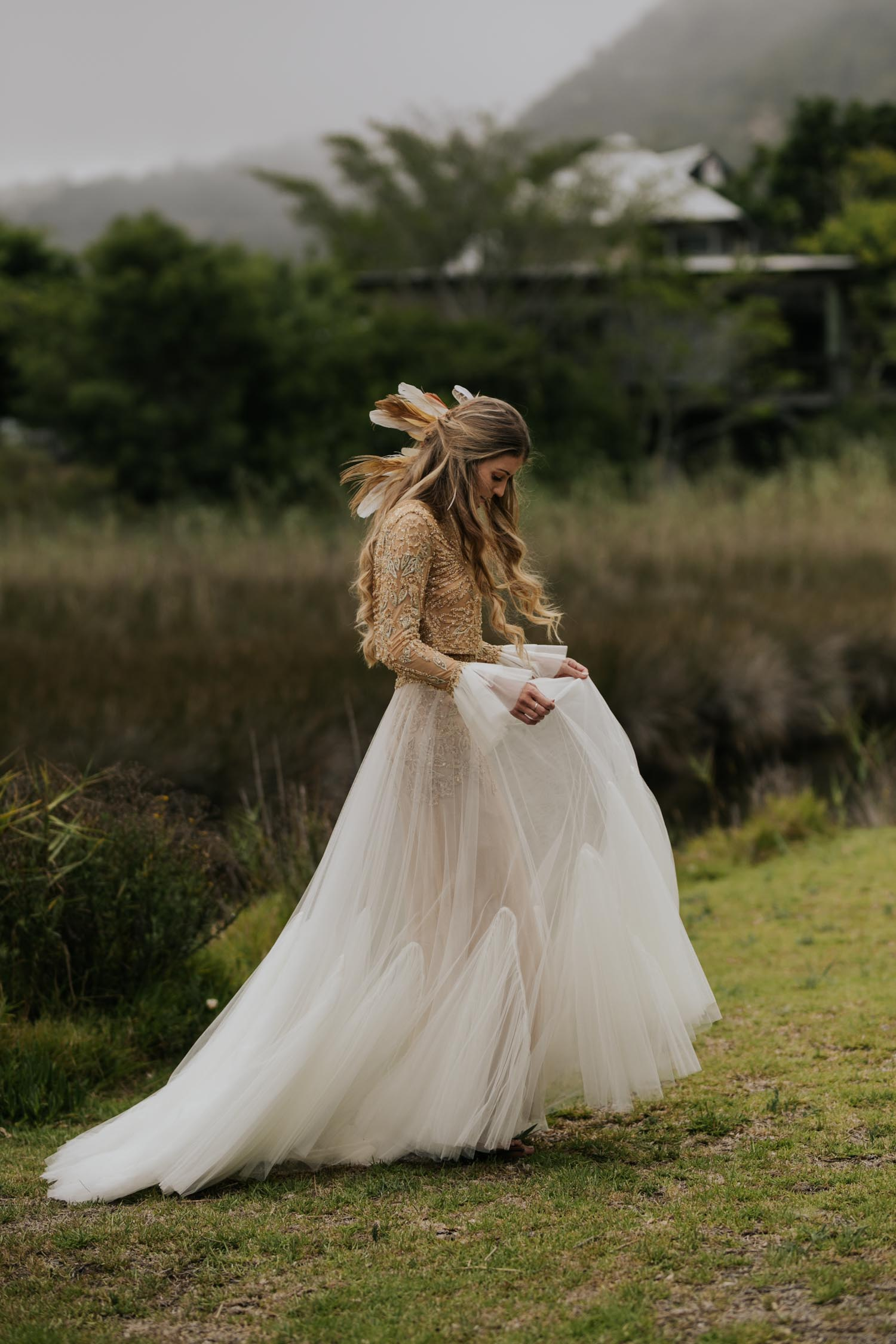 Bohemian bride with long curly blonde hair wears two piece gold and cream long sleeve wedding dress and feathers and plait in her hair shows off her dress