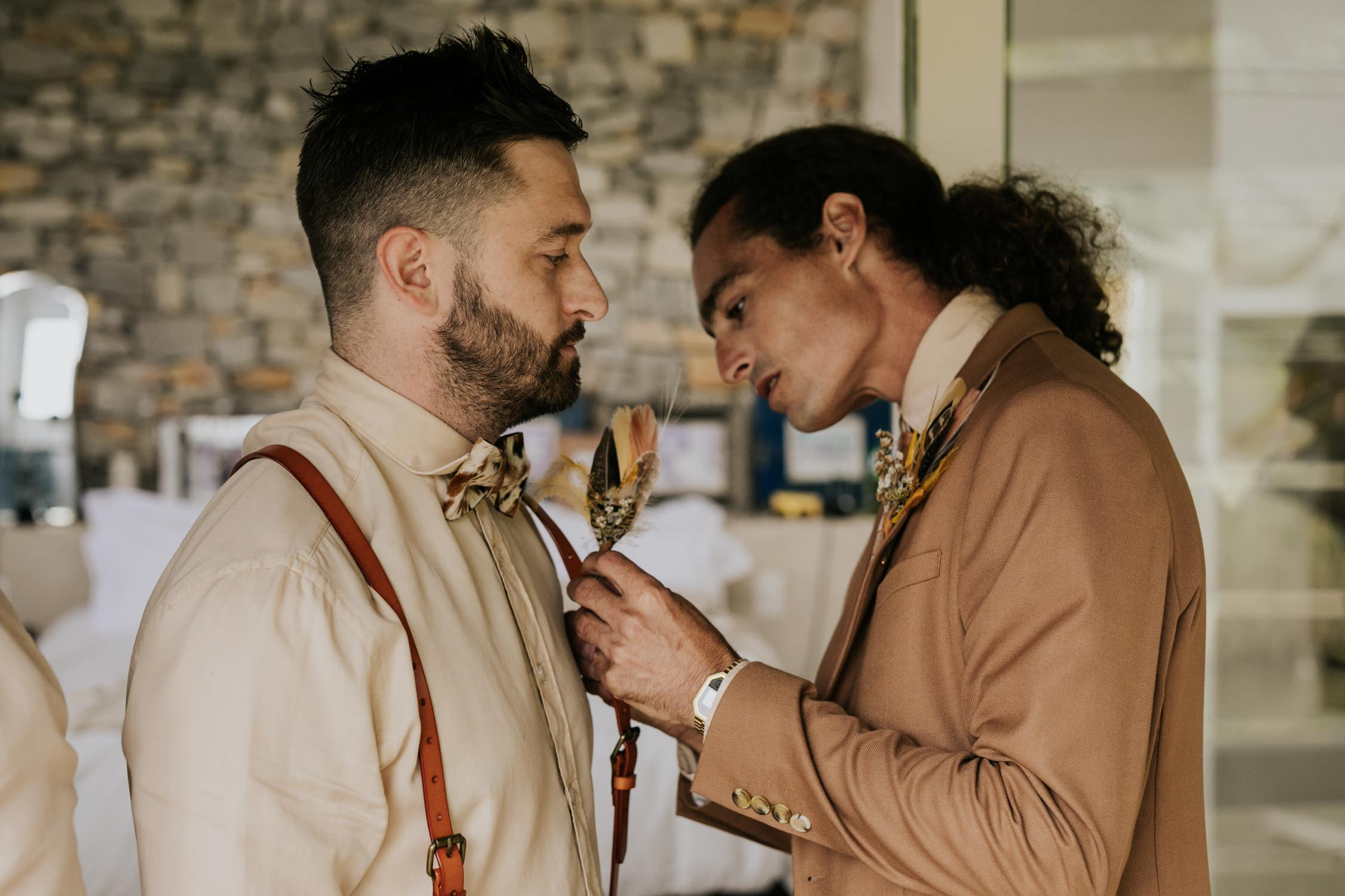 Groom put on foraged feather and dried flower boutineers for his boho gypsy style wedding