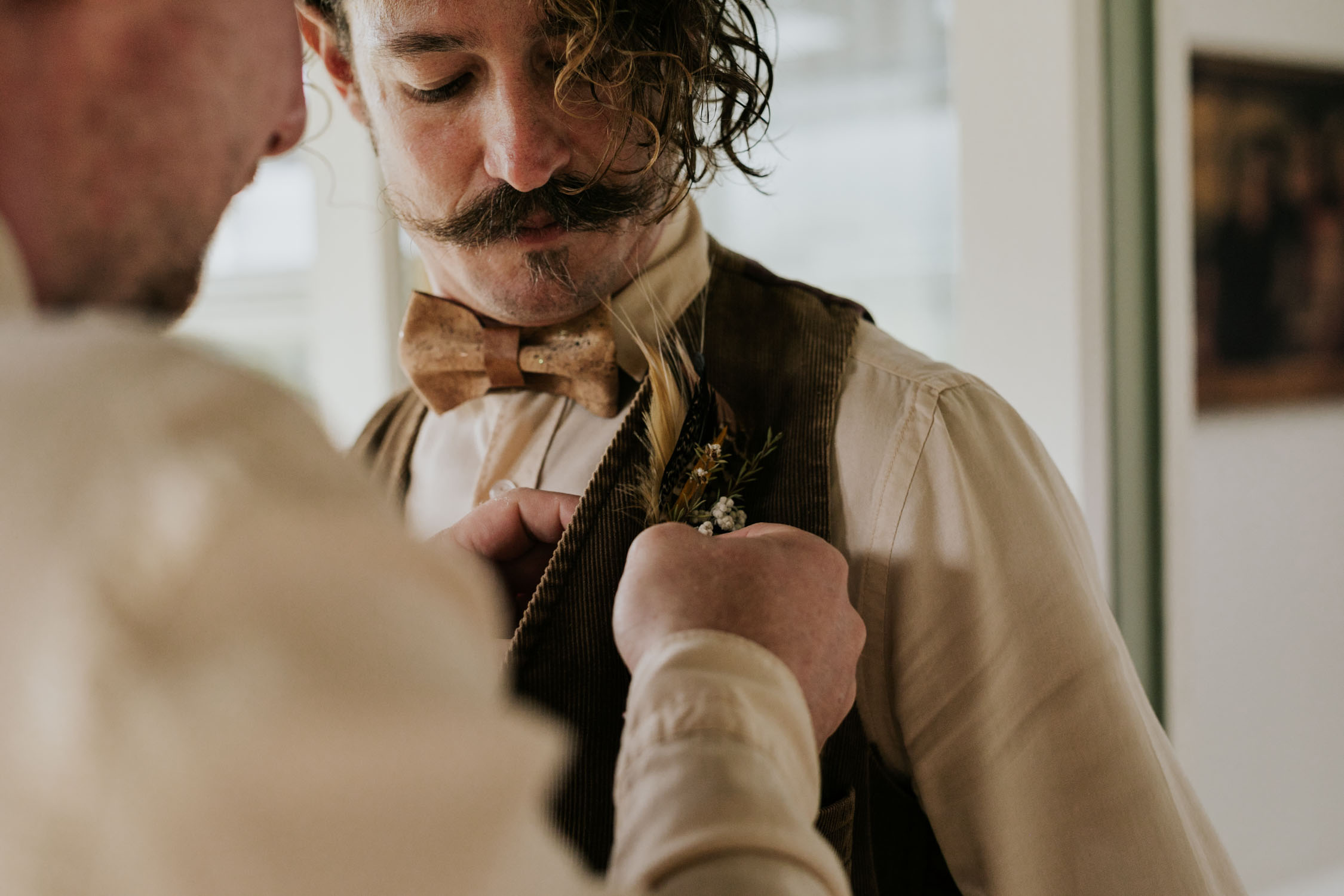 Groomsman puts on foraged feather and dried flower boutineers for bohemian gypsy style wedding