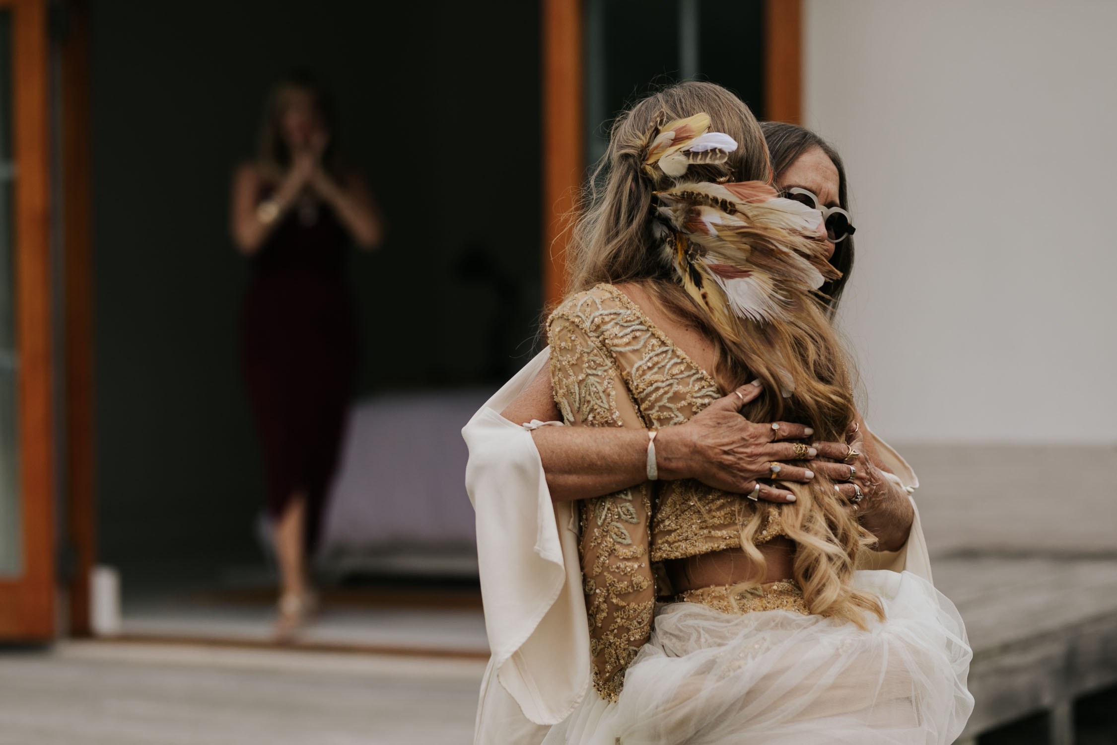 Bohemian bride with long curly blonde hair wears two piece gold and cream long sleeve wedding dress and feathers and plait in her hair hugs her mother in law