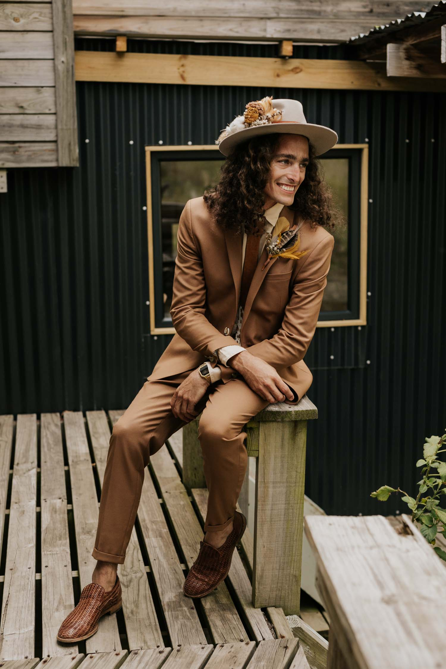 Groom wears brown suite, beige shirt, brown Nguni cowhide tie, felt hat and foraged dried flowers and feather boutineer