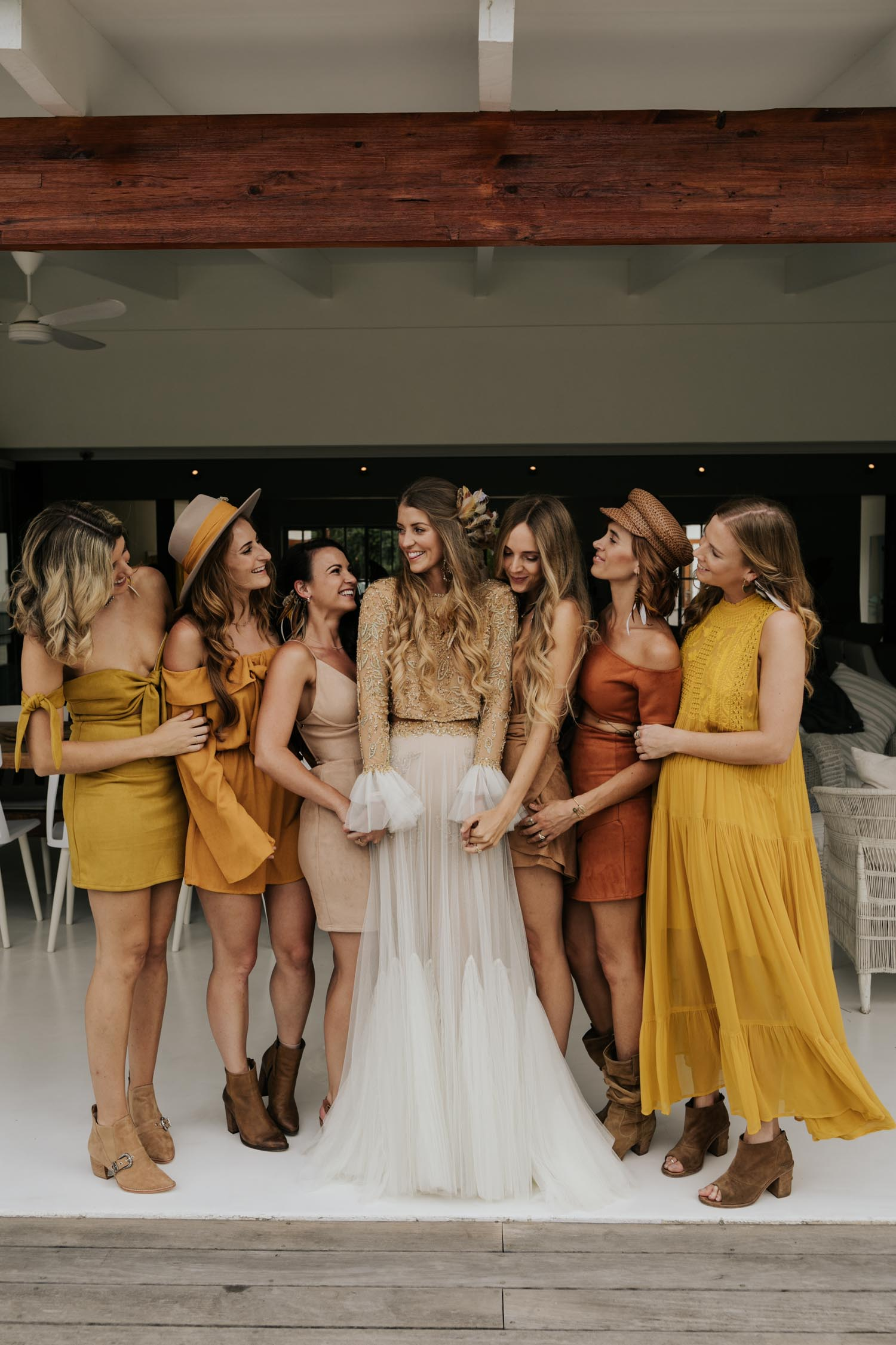 The ultimate boho gypsy bride tribe wearing gypsy sunshine and rust coloured dresses and hats