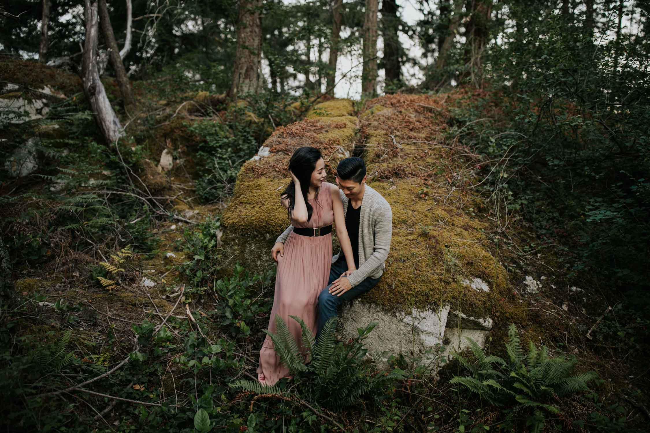 Couple laugh together on moss covered rock in forest in the best location for Engagement Shoot in Vancouver, Lighthouse Park