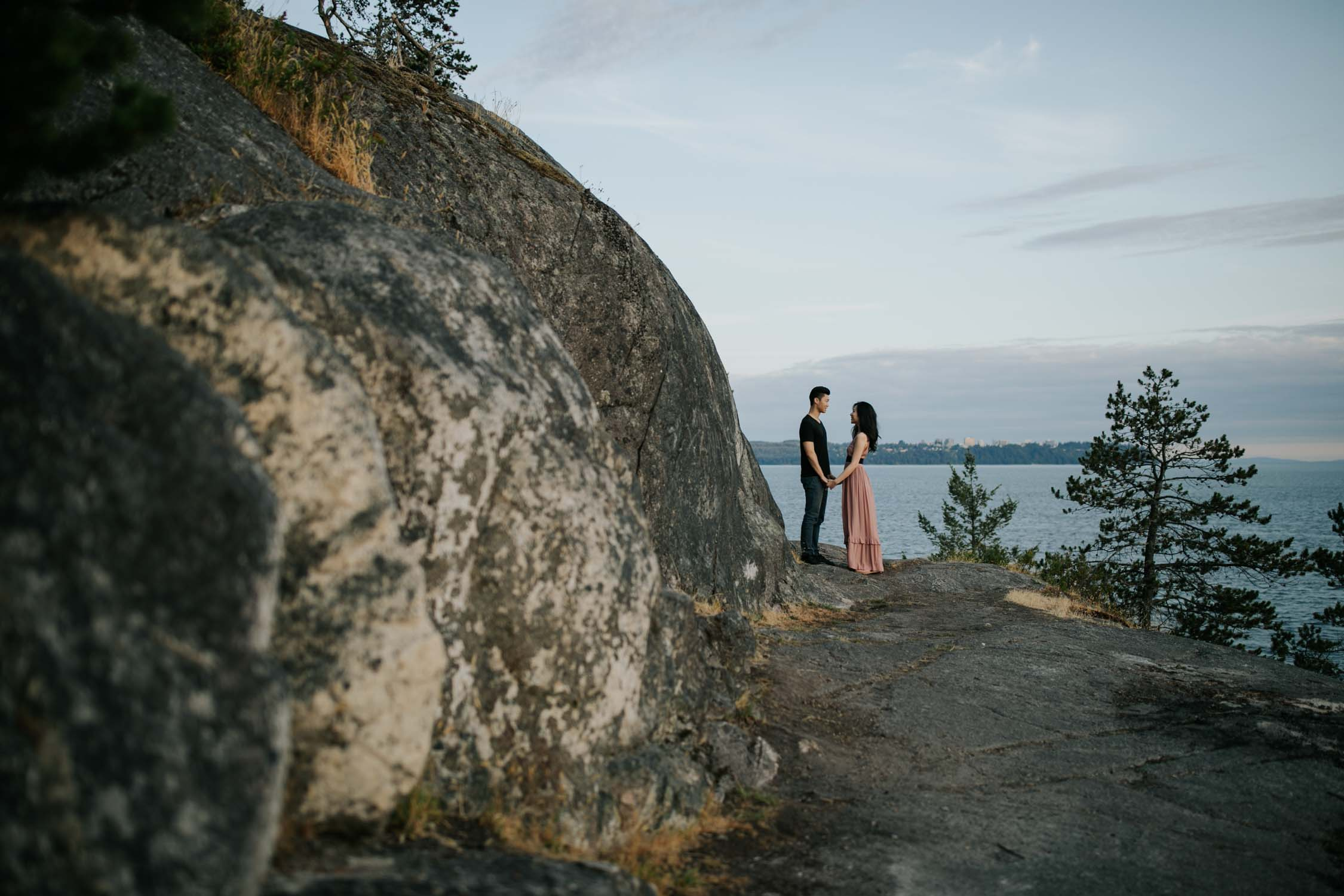 Beautiful Asian couple stand on grey rocks in Lighthouse Park overlooking breathtaking views