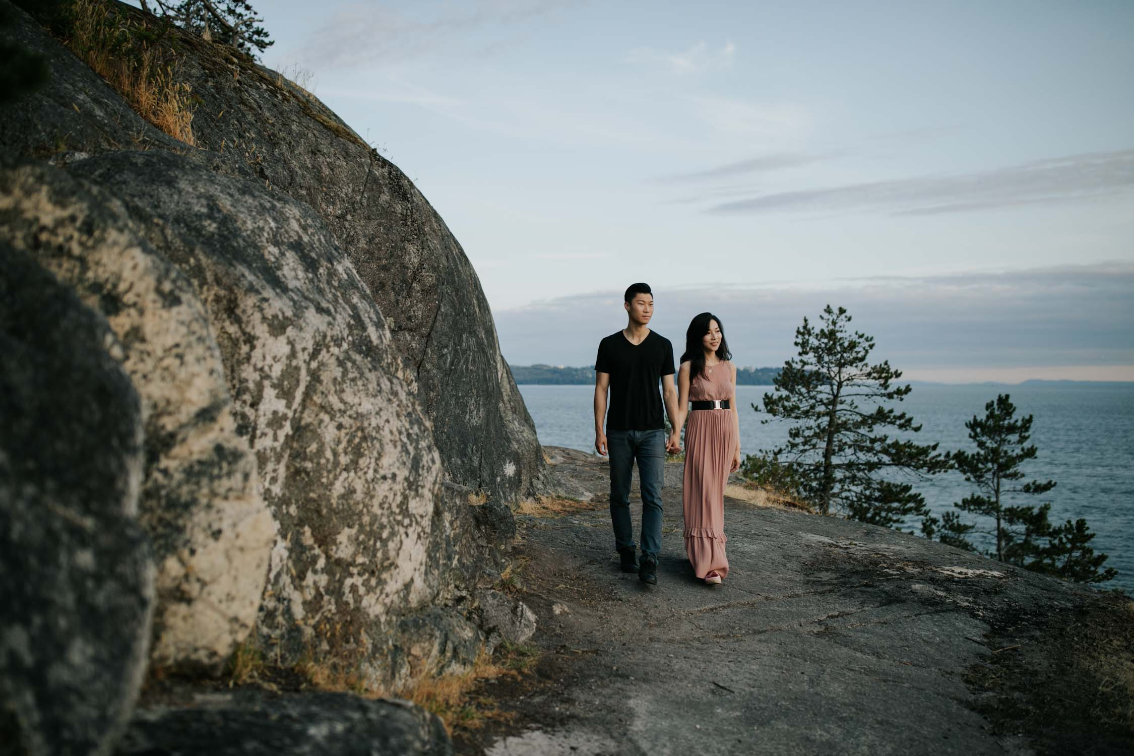 Candid and natural engagement shoot photo of couple walking on rocks in Lighthouse Park with ocean and forest views