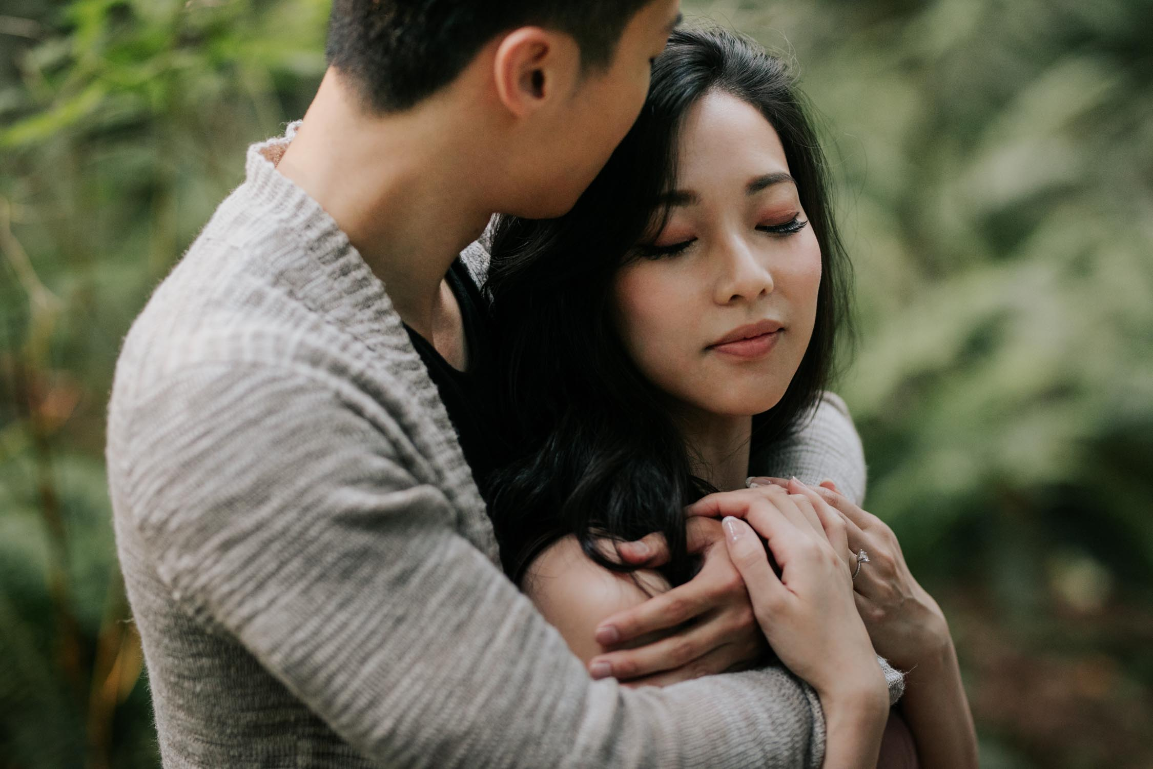 Couple embrace in Lighthouse Park forest with guy kissing beautiful Asian girl on the top of her head