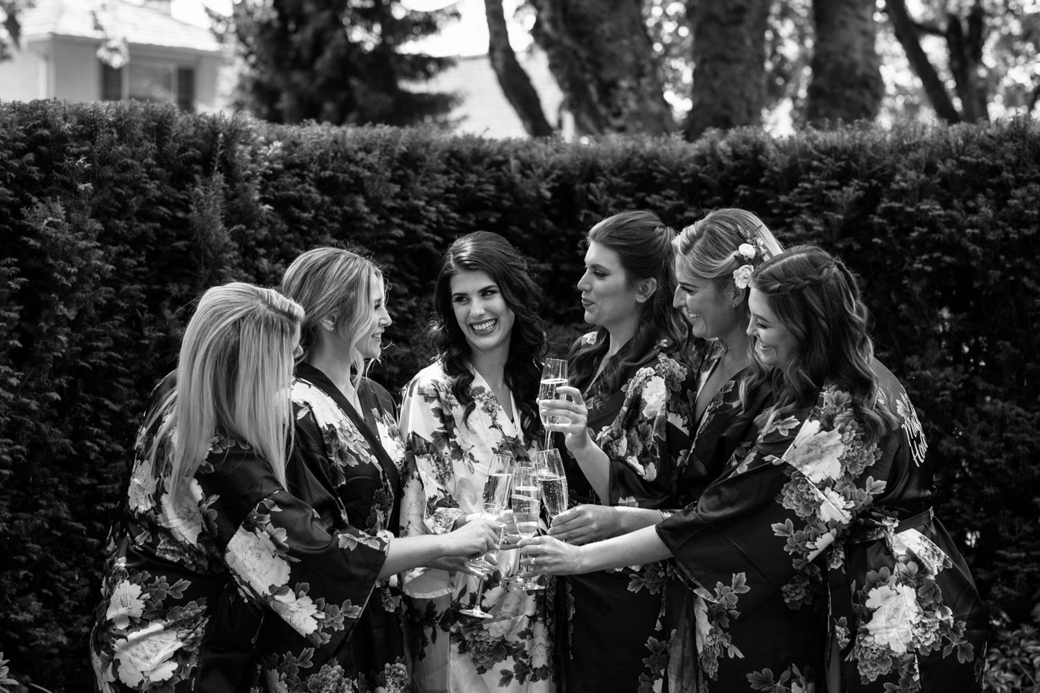Fun champagne toast with beautiful bride with her bride tribe wearing floral robes in the garden