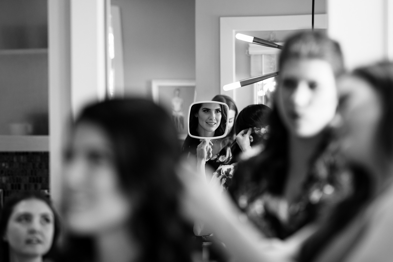 Candid moment of bride looking in the mirror while Vancouver makeup artist, Save The Date Beauty Vancouver makeup, applies her makeup