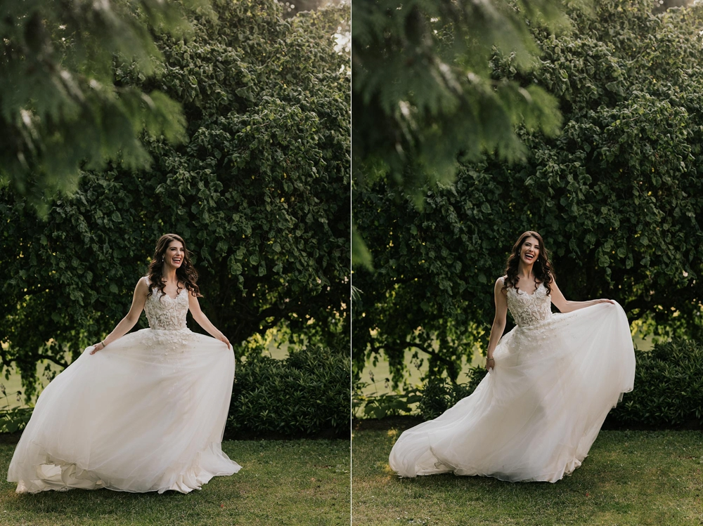 Gorgeous brunette bride laughs and shows off her perfect lace dress in the gardens at Brock House Restaurant