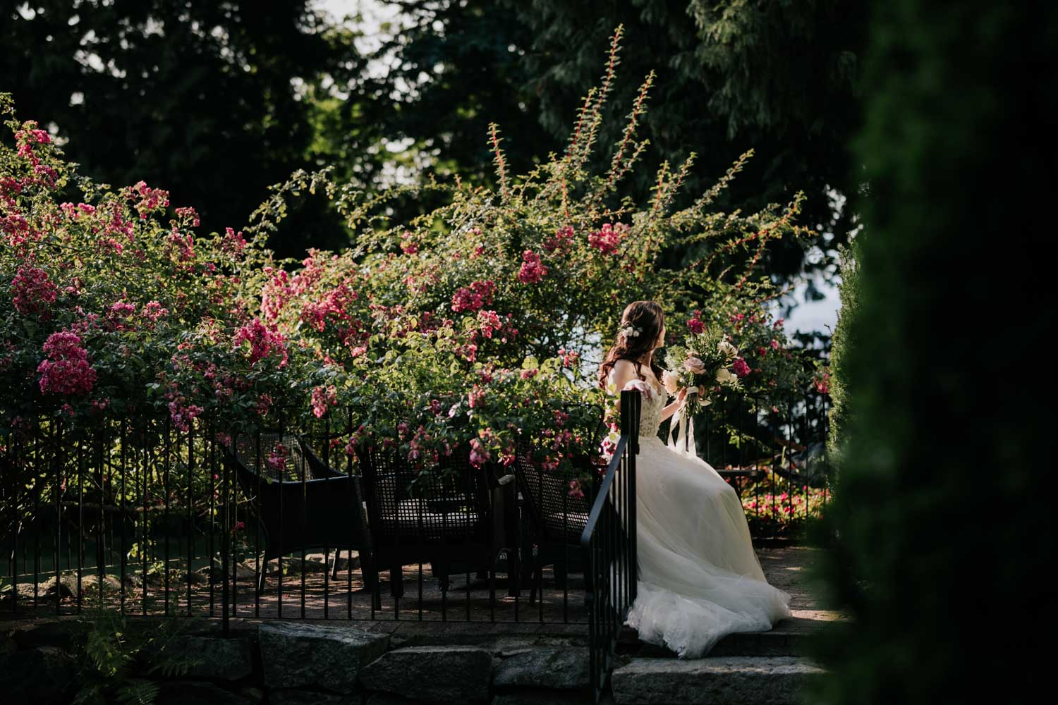 Gorgeous bride sitting on chair in the sun in beautiful garden at best Vancouver heritage house wedding venue, Brock House