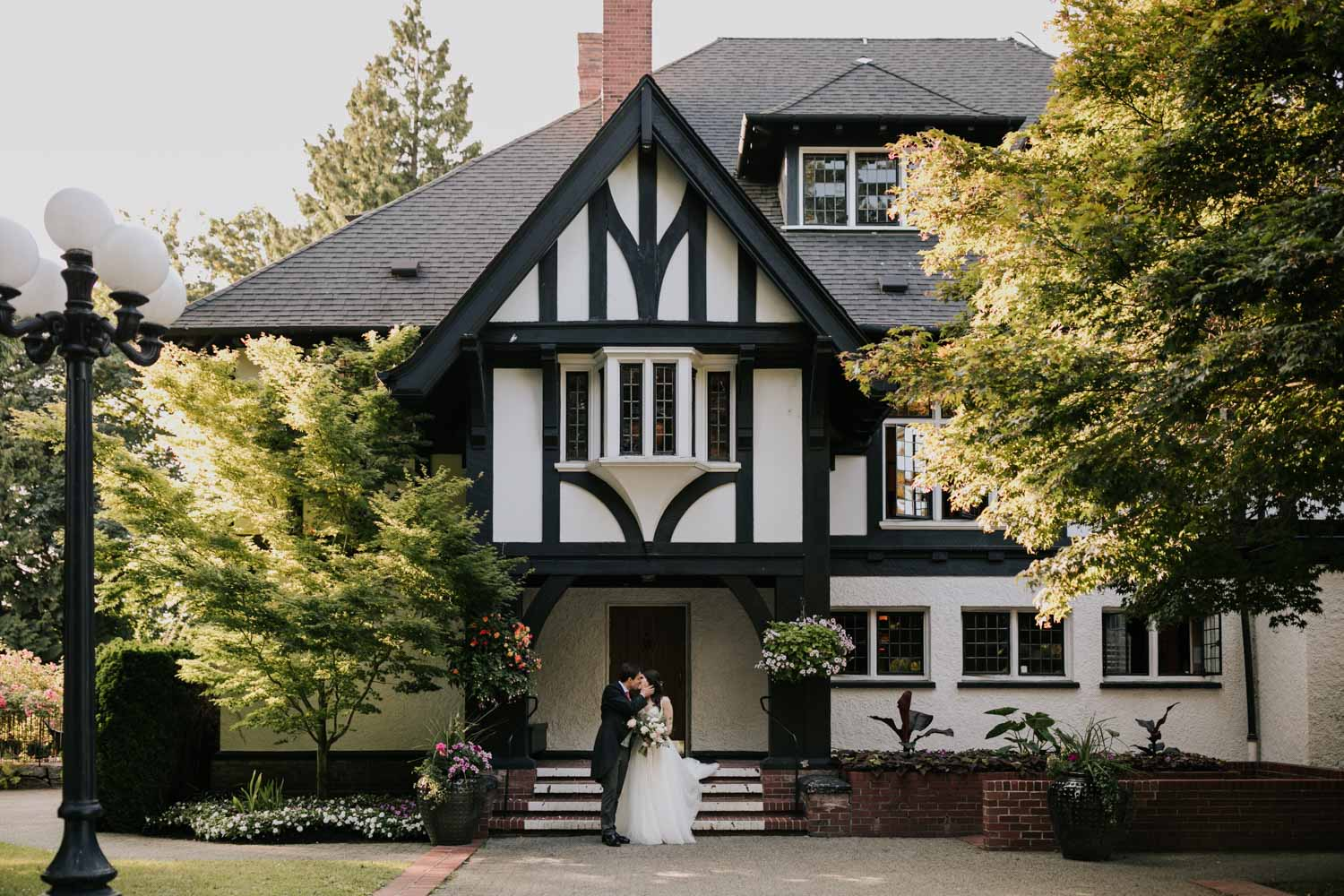 Beautiful bride and groom stand outside front entrance to gorgeous old heritage building and wedding venue in Vancouver, Brock House Restaurant