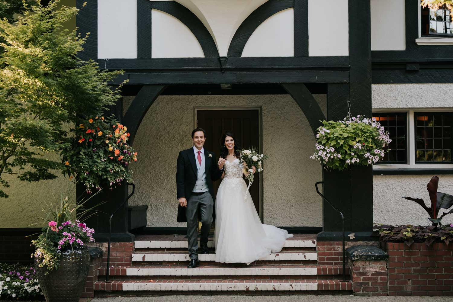 Happy bride and groom stand outside front entrance to gorgeous old heritage building and wedding venue in Vancouver, Brock House Restaurant