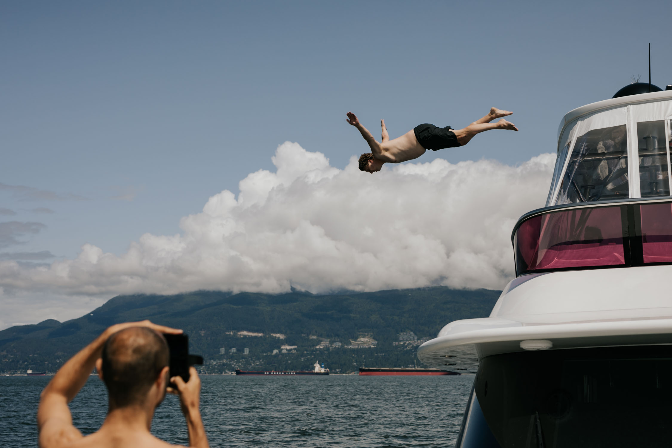 Groomsman takes photo of another groomsman diving off yacht before wedding