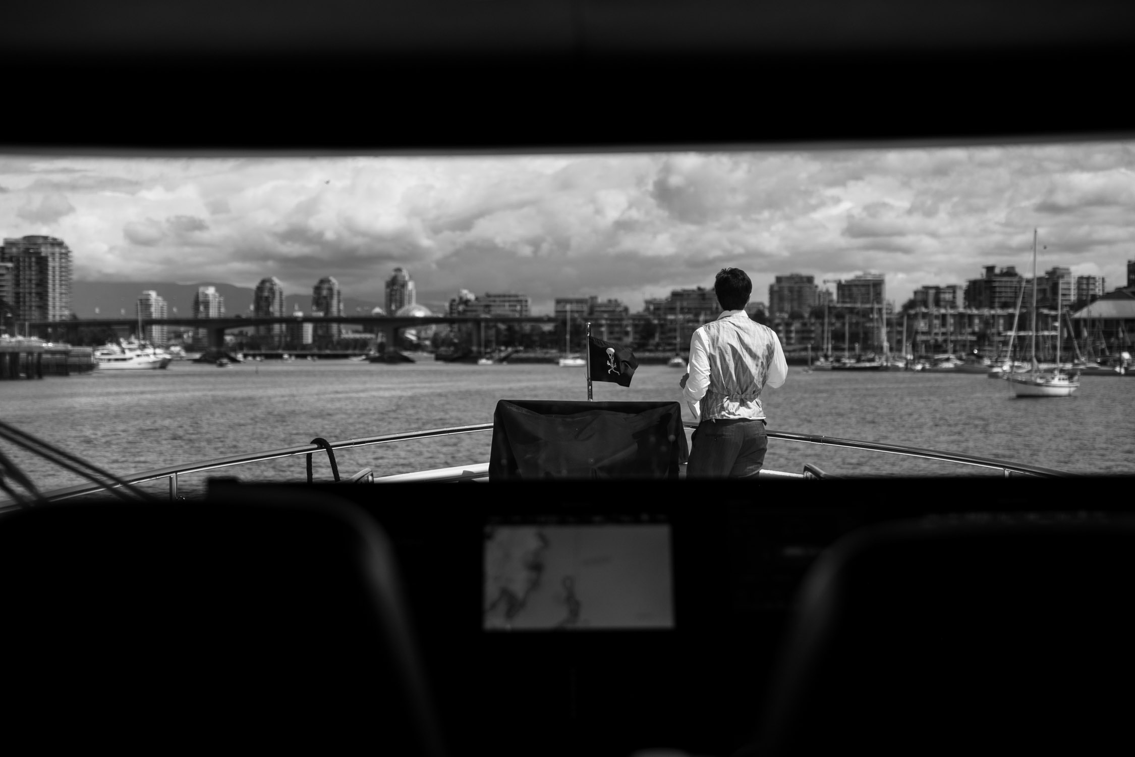 Groom stands on yacht looking at downtown Vancouver views before his wedding ceremony at Christ Church Cathedral