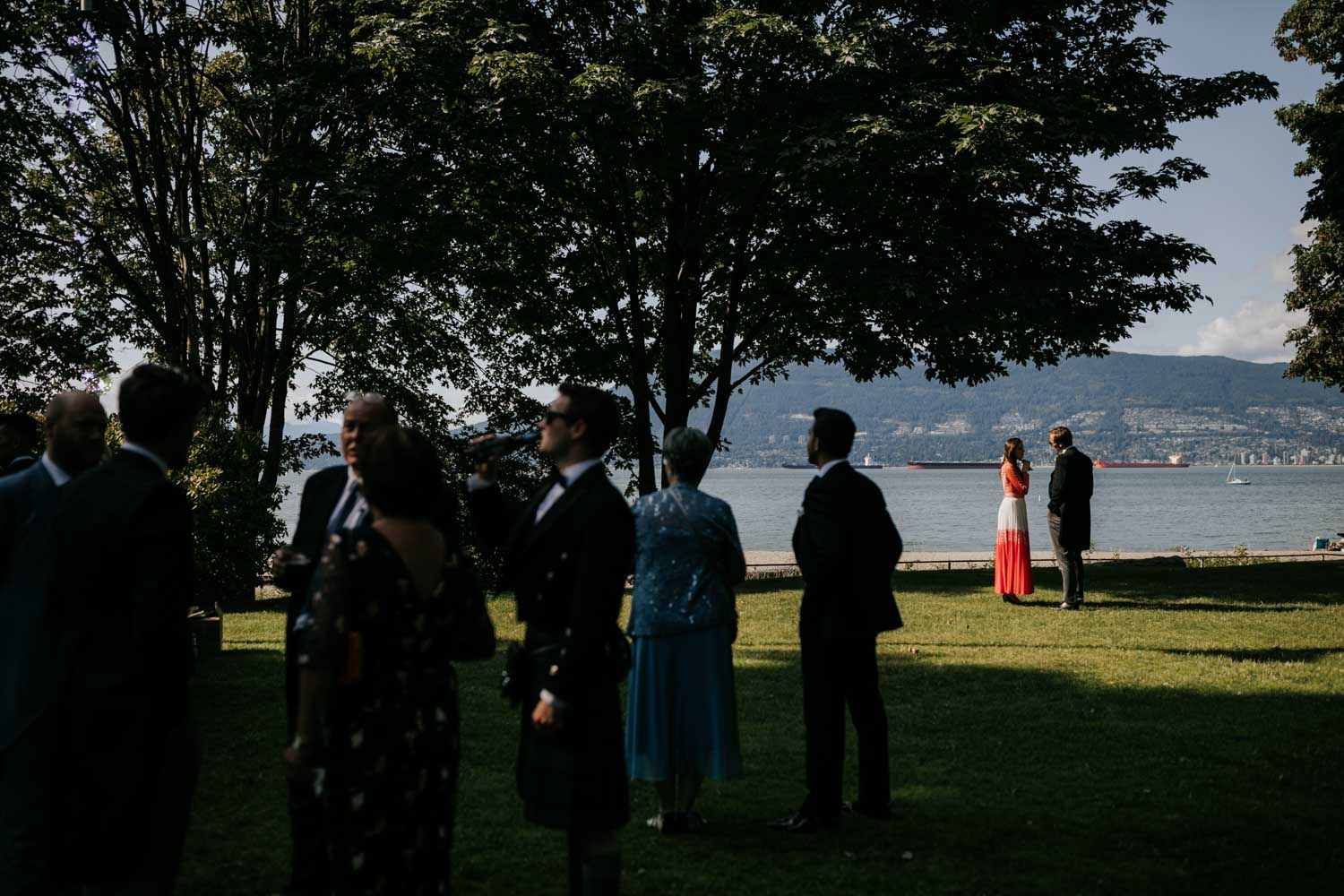 Wedding guest in the sun on the lawn overlooking the sea during cocktail hour at Brock House Restaurant Wedding Venue on Jericho Beach
