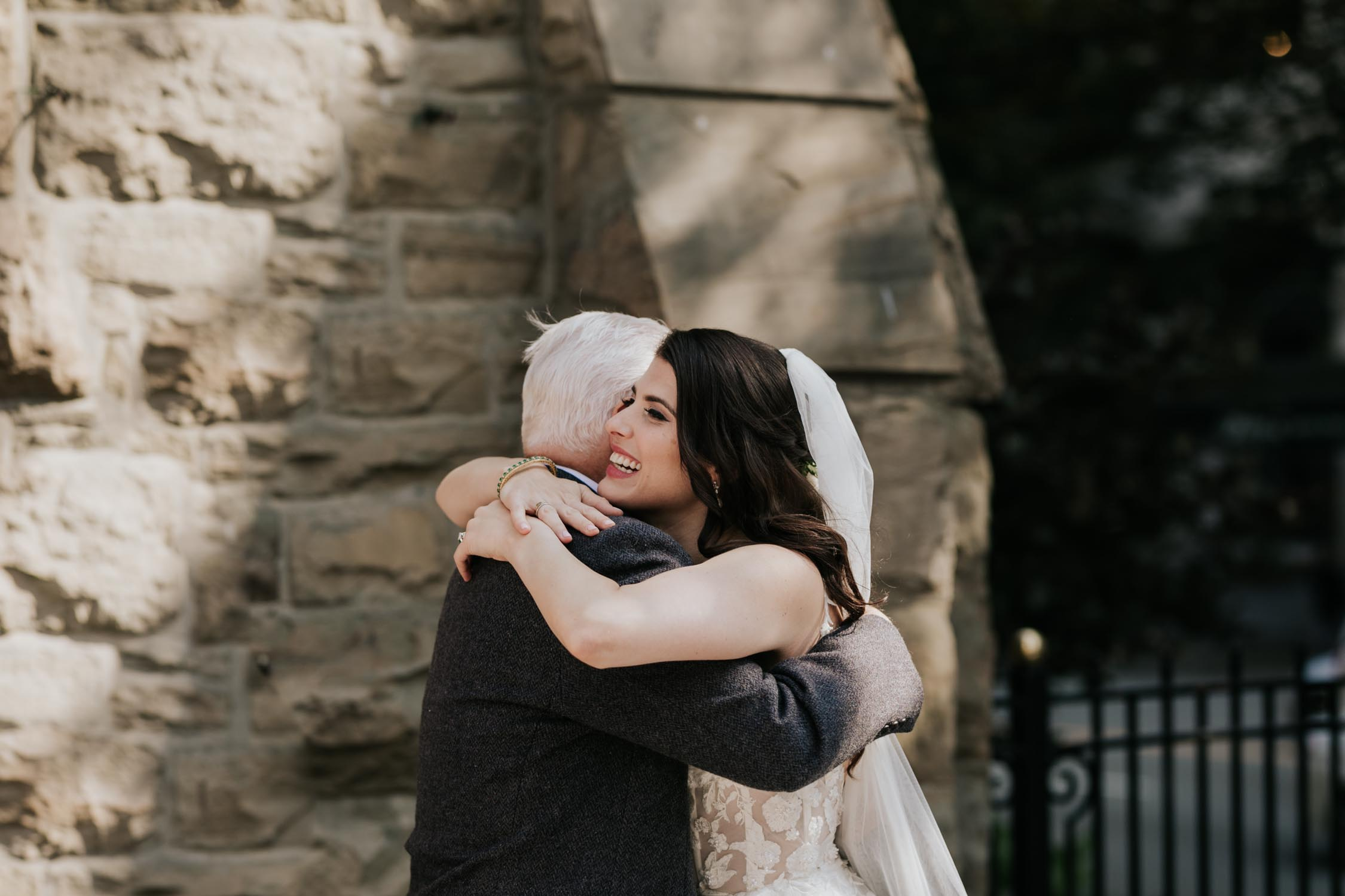 Elated bride is hugged and congratulated by her father at Christ Church Cathedral in Vancouver