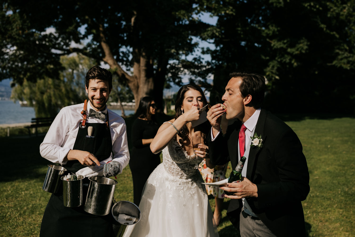 Bride and groom eating fresh shucked oysters on lawn during cocktail hour at Brock House Restaurant Wedding Venue on Jericho Beach