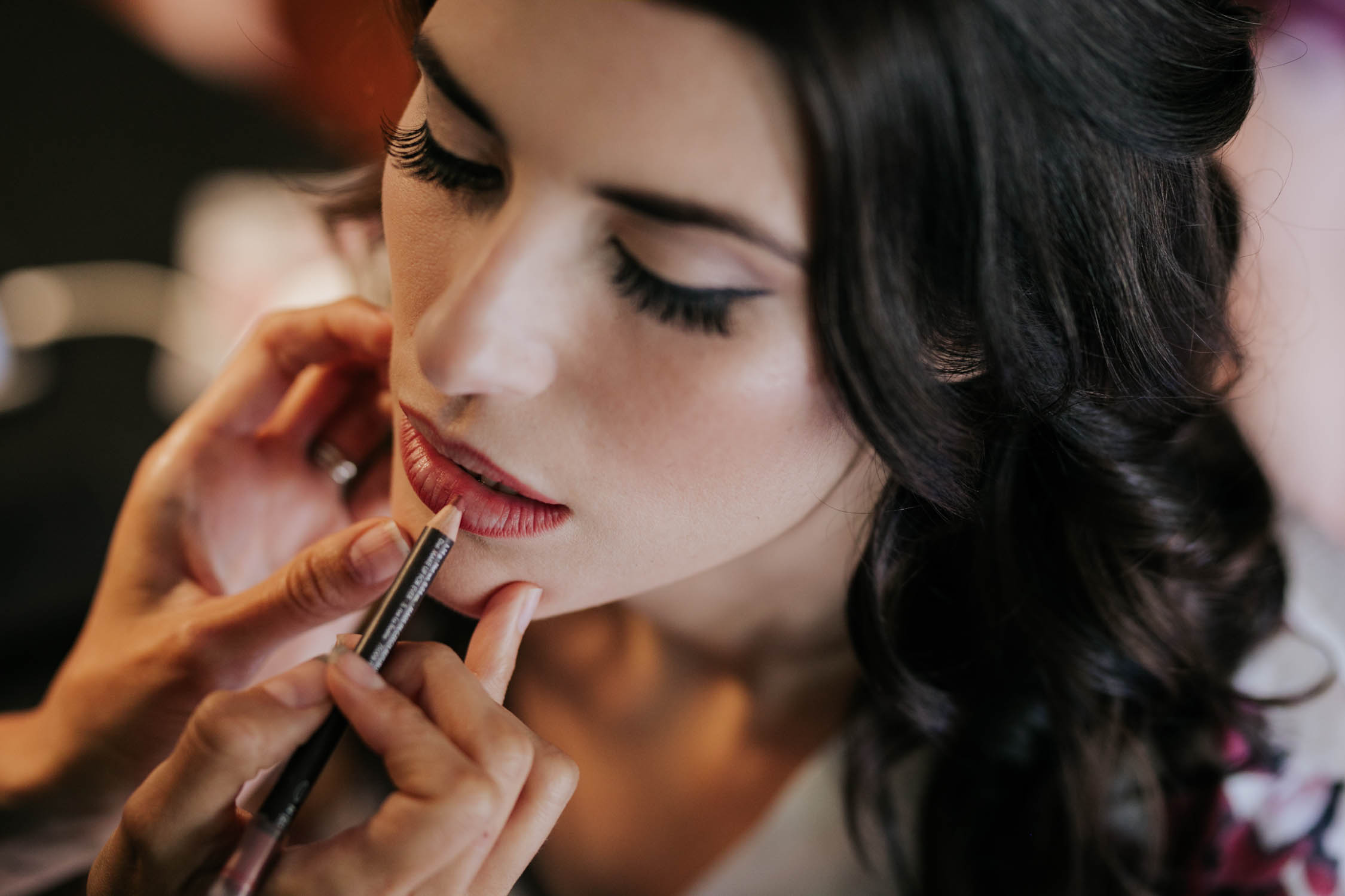 Bird's eye view high angle of Save The Date Beauty putting read lipliner and lipstick on beautiful natural brunette bride