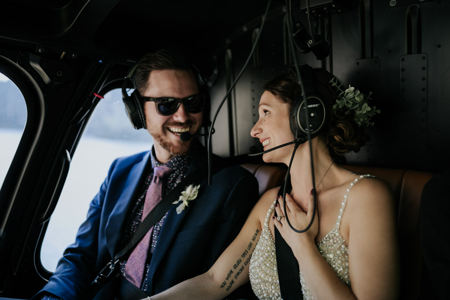 Bride and groom hold hands in helicopter as it flies over Vancouver mountains to secluded location for real elopement in the mountains of Vancouver