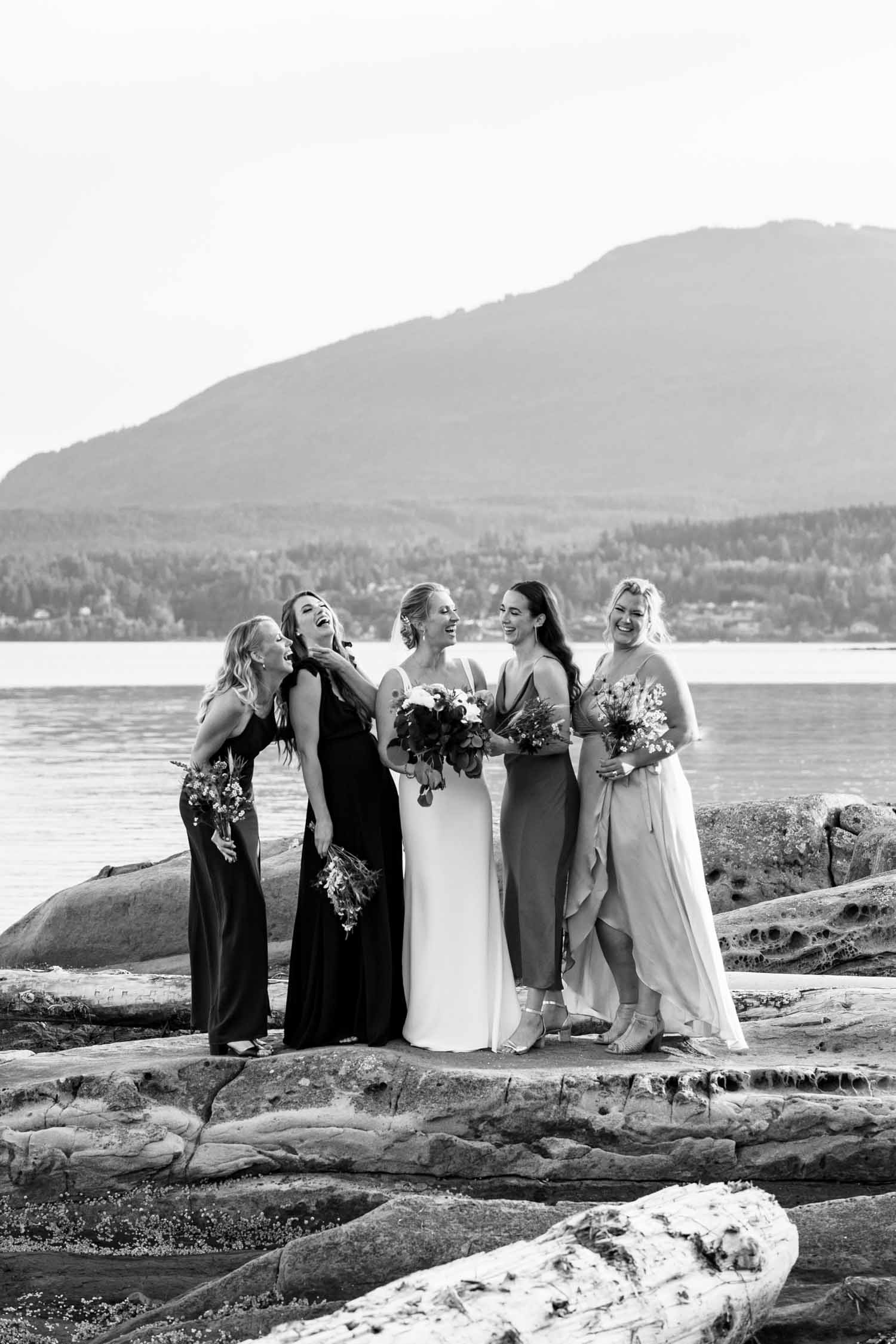 Candid happy photo of bride and bridesmaids laughing on rocks at the seaside at Vancouver Island wedding