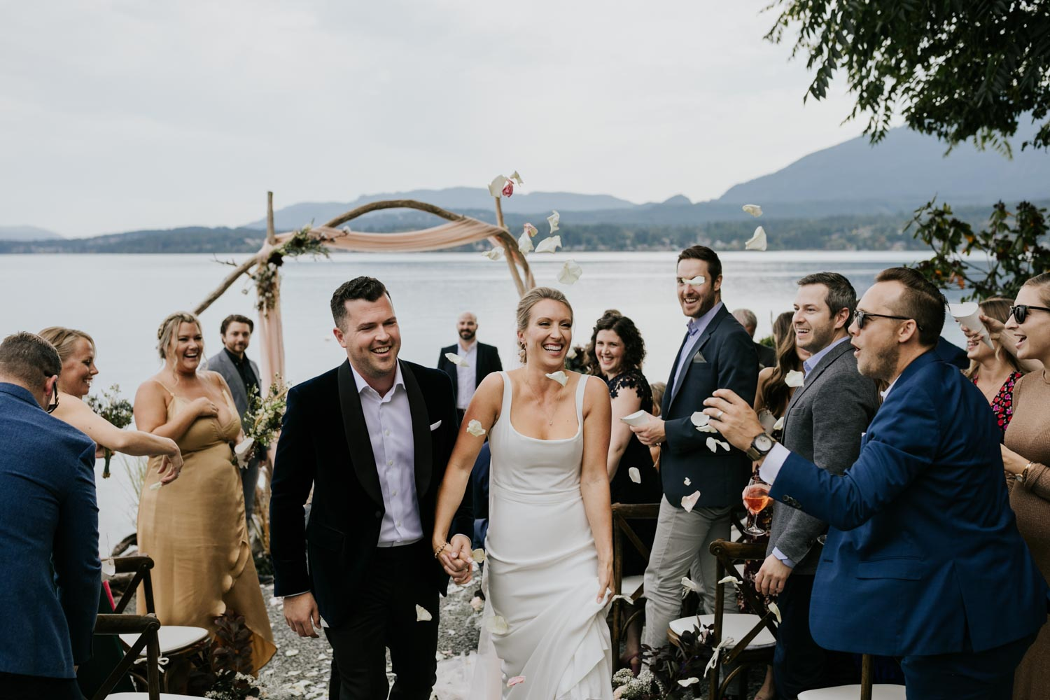 Bride and groom confetti toss at the beach on Vancouver Island under wooden arch decorated with dusty pink fabric, raw cotton stems, pampas grass and dried flowers