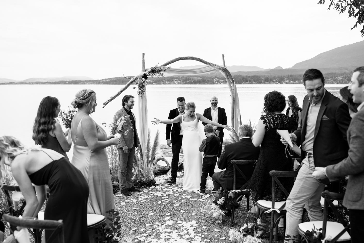 Bride and groom get married at the beach on Vancouver Island under wooden arch decorated with dusty pink fabric, raw cotton stems, pampas grass and dried flowers