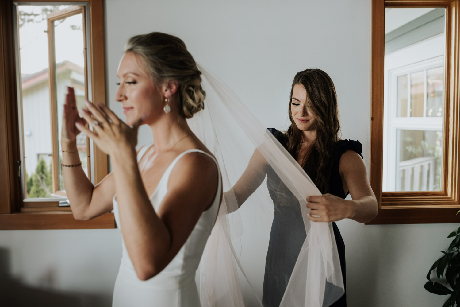 Bride crying as sister puts on her alternative blush pink veil