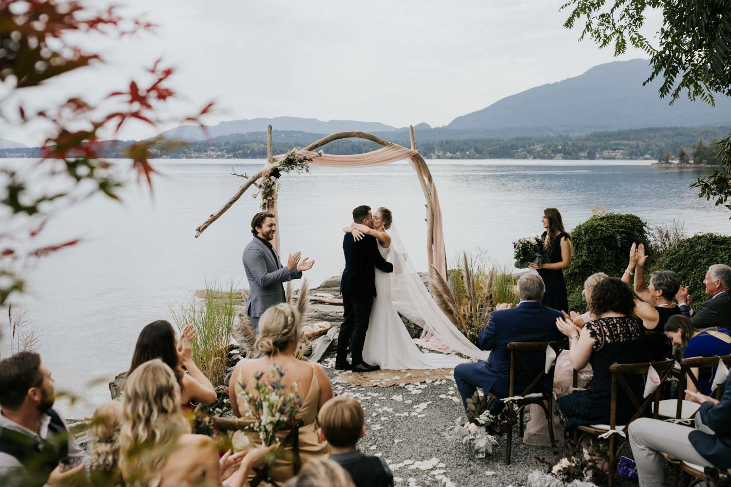 Bride and groom first kiss at the beach on Vancouver Island under wooden arch decorated with dusty pink fabric, raw cotton stems, pampas grass and dried flowers