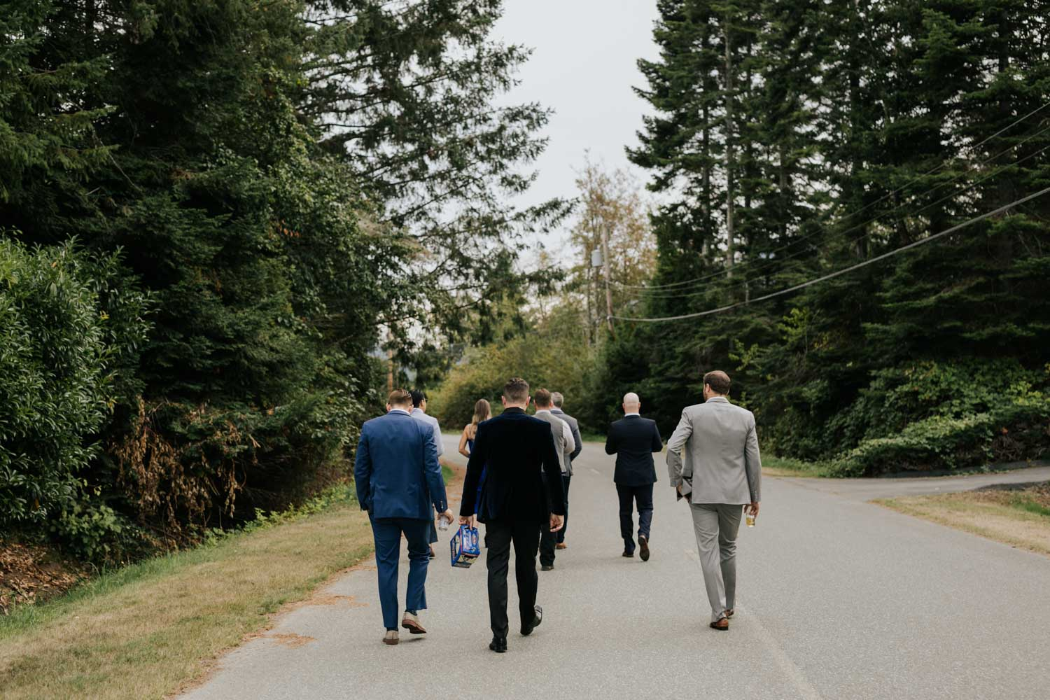 Candid getting ready photos of groom and groomsmen walking down road with beers on Vancouver Island