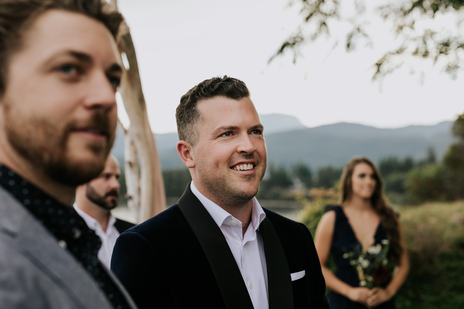 Groom's happy reaction as he watches his soon to be wife walk down the aisle towards him