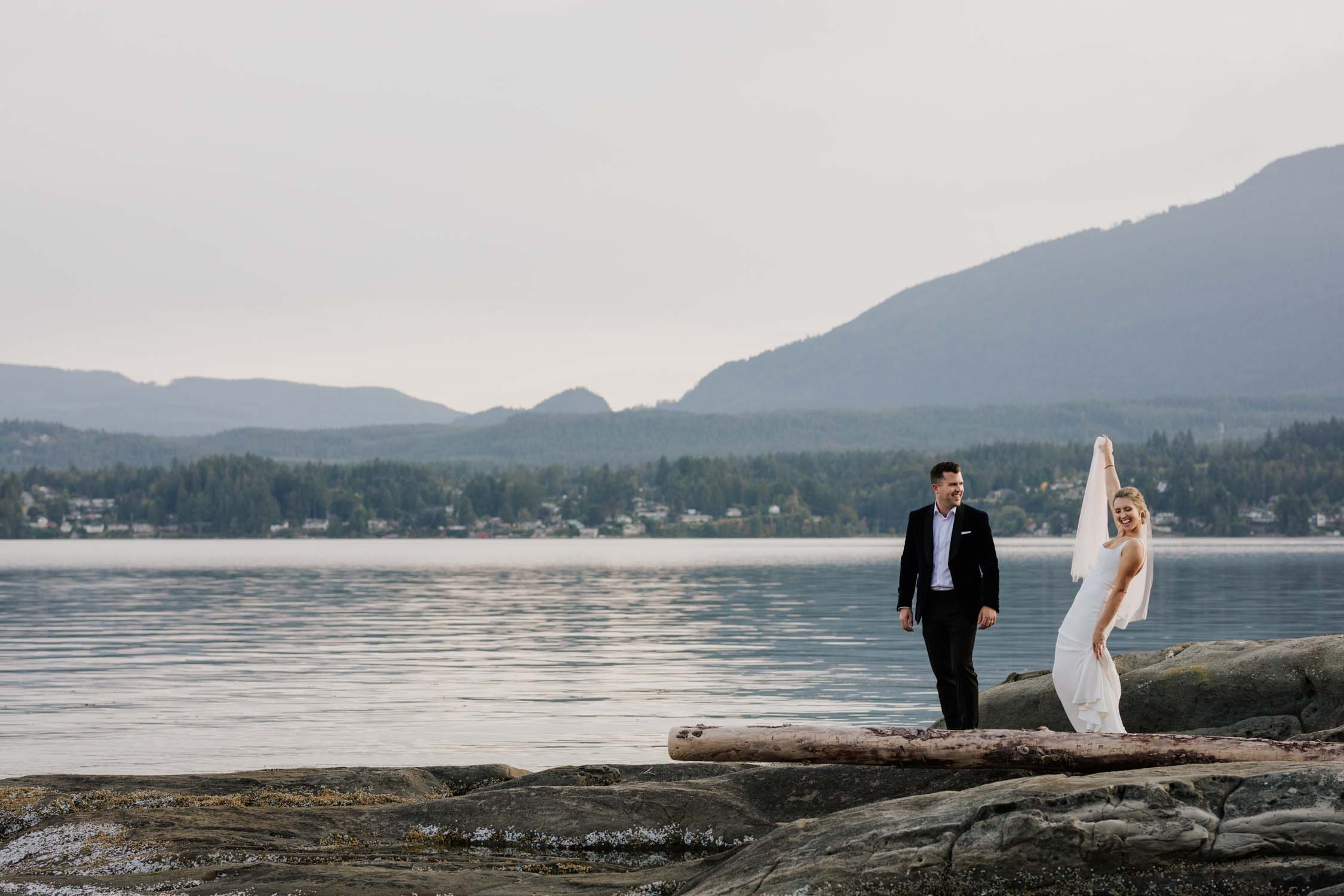 Fun wedding photo taken at the beach with sea and mountain views on Vancouver Island