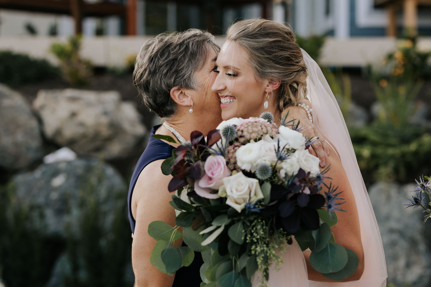 Mom hugs bride who is holding beautiful wedding bouquet of soft pinks, greys, burgundy and subtle green