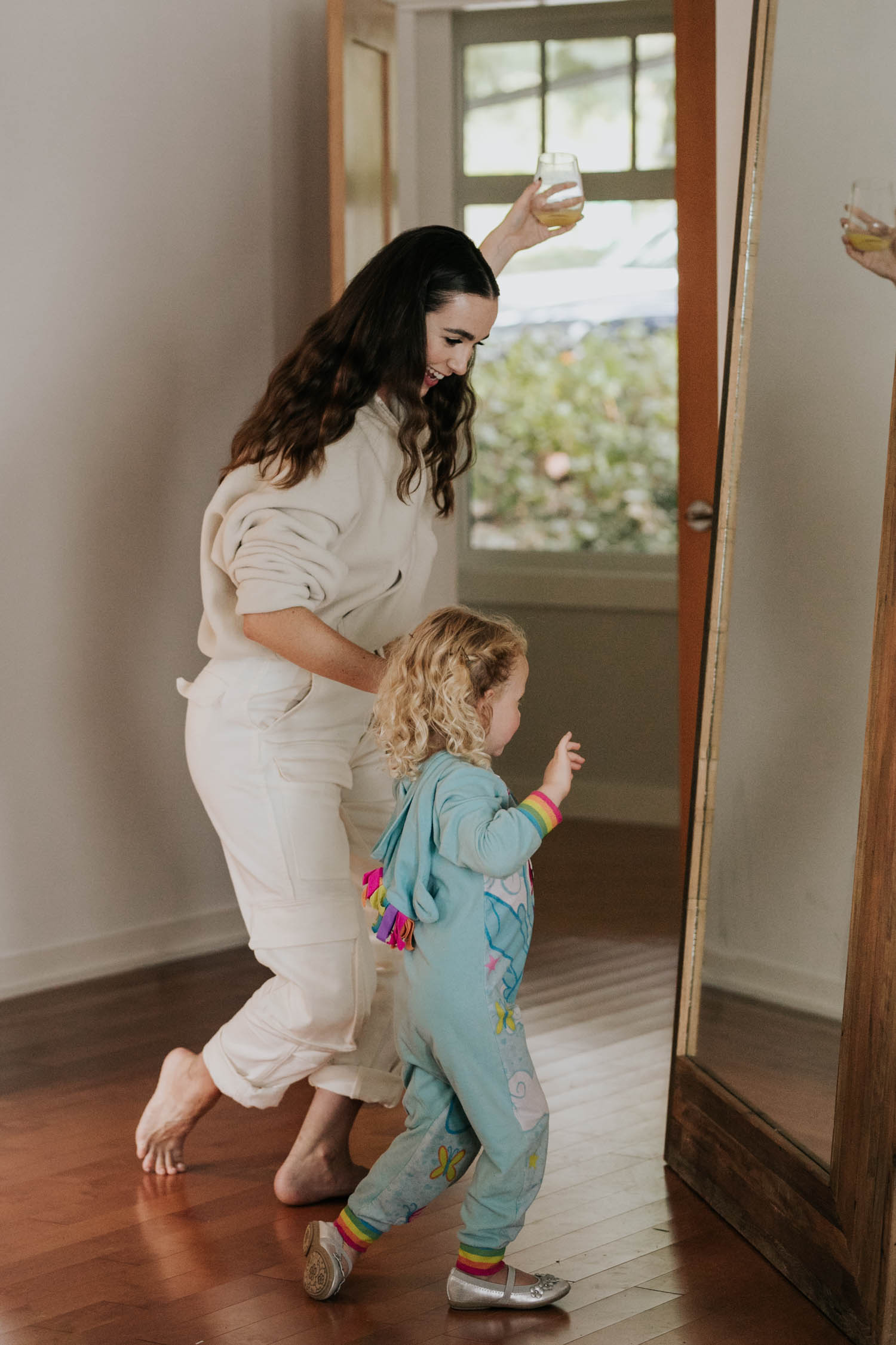 Bridesmaid and flower girl wearing unicorn onesie dance in front of the mirror